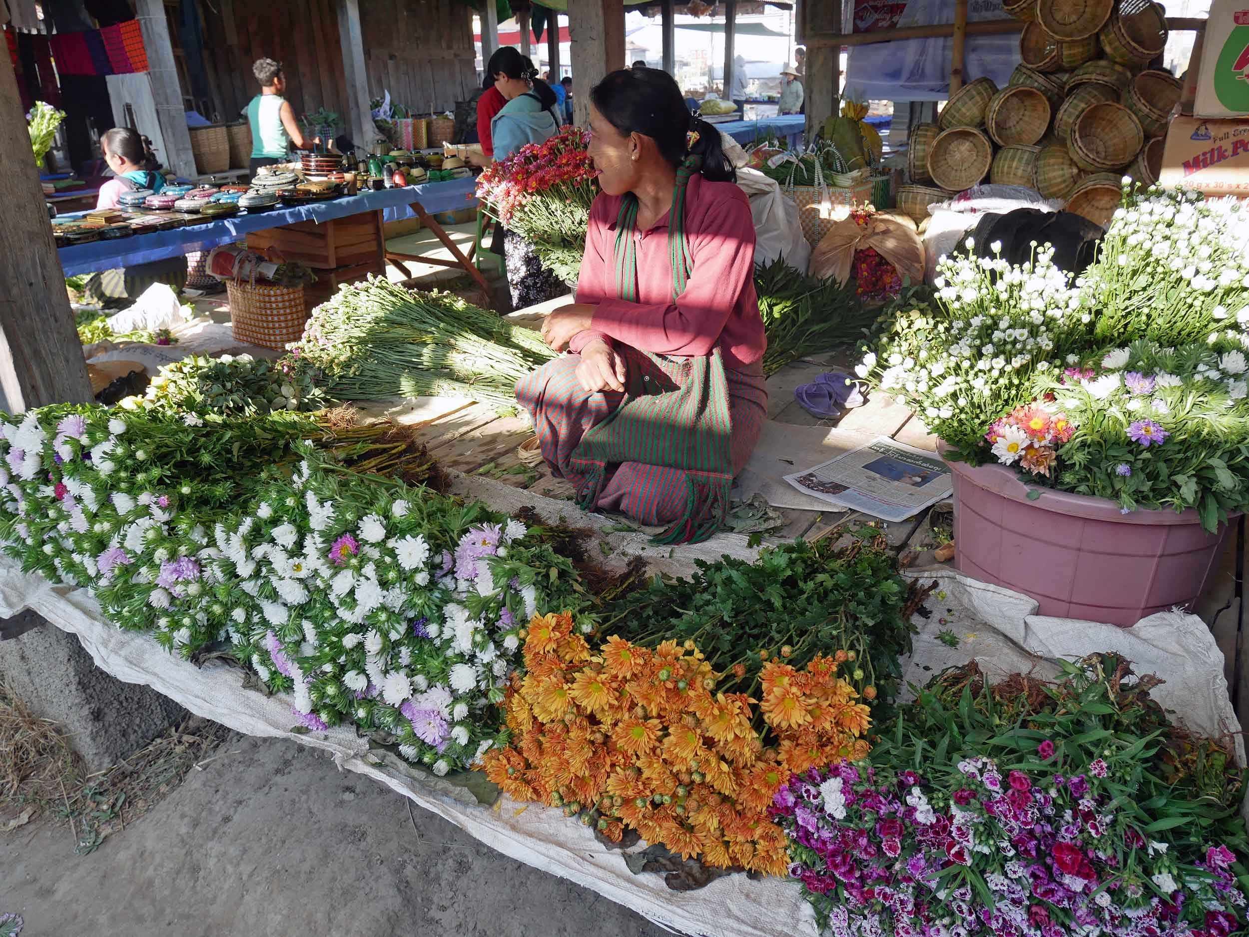 Vibrant fresh flowers are sold at market (note the roots still attached) (Feb 22).