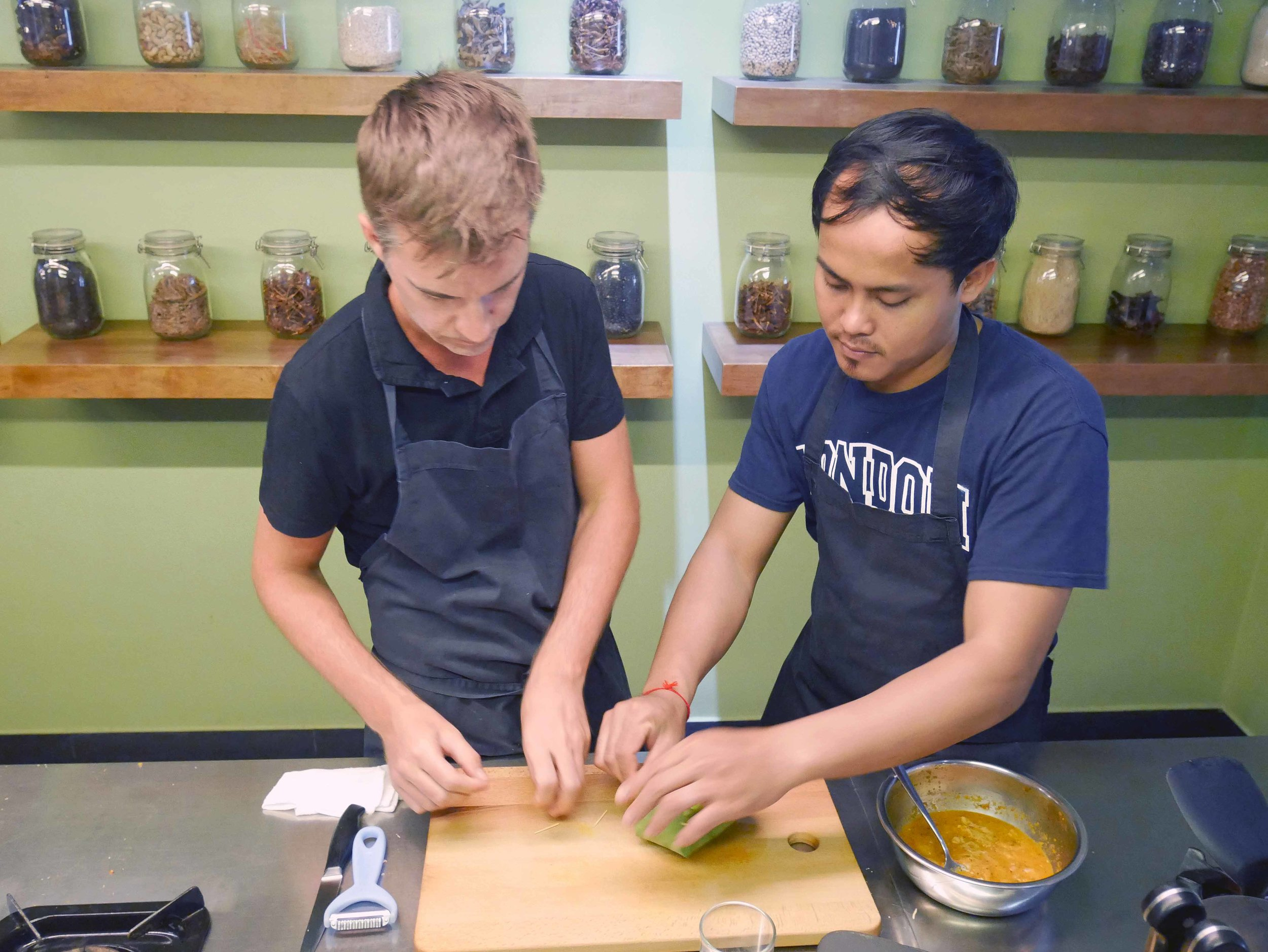 Trey gets help from Khai, our instructor, to fashion a bowl from banana leaf for the Amok dish (March 10).