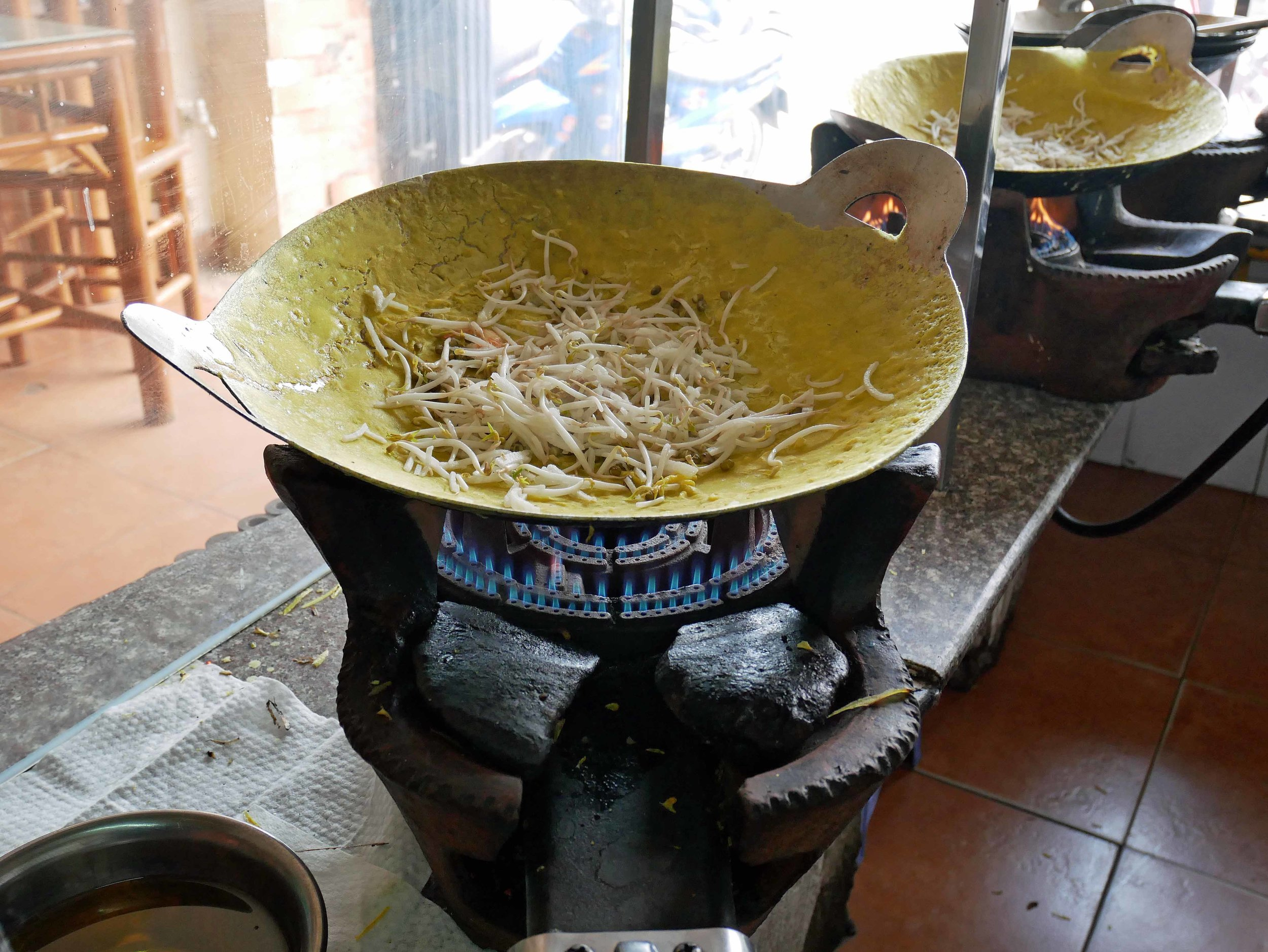 To make Banh Xeo, our lunch that day, the cook spreads rice batter very thin in a wok before adding shrimp, pork and bean sprouts.