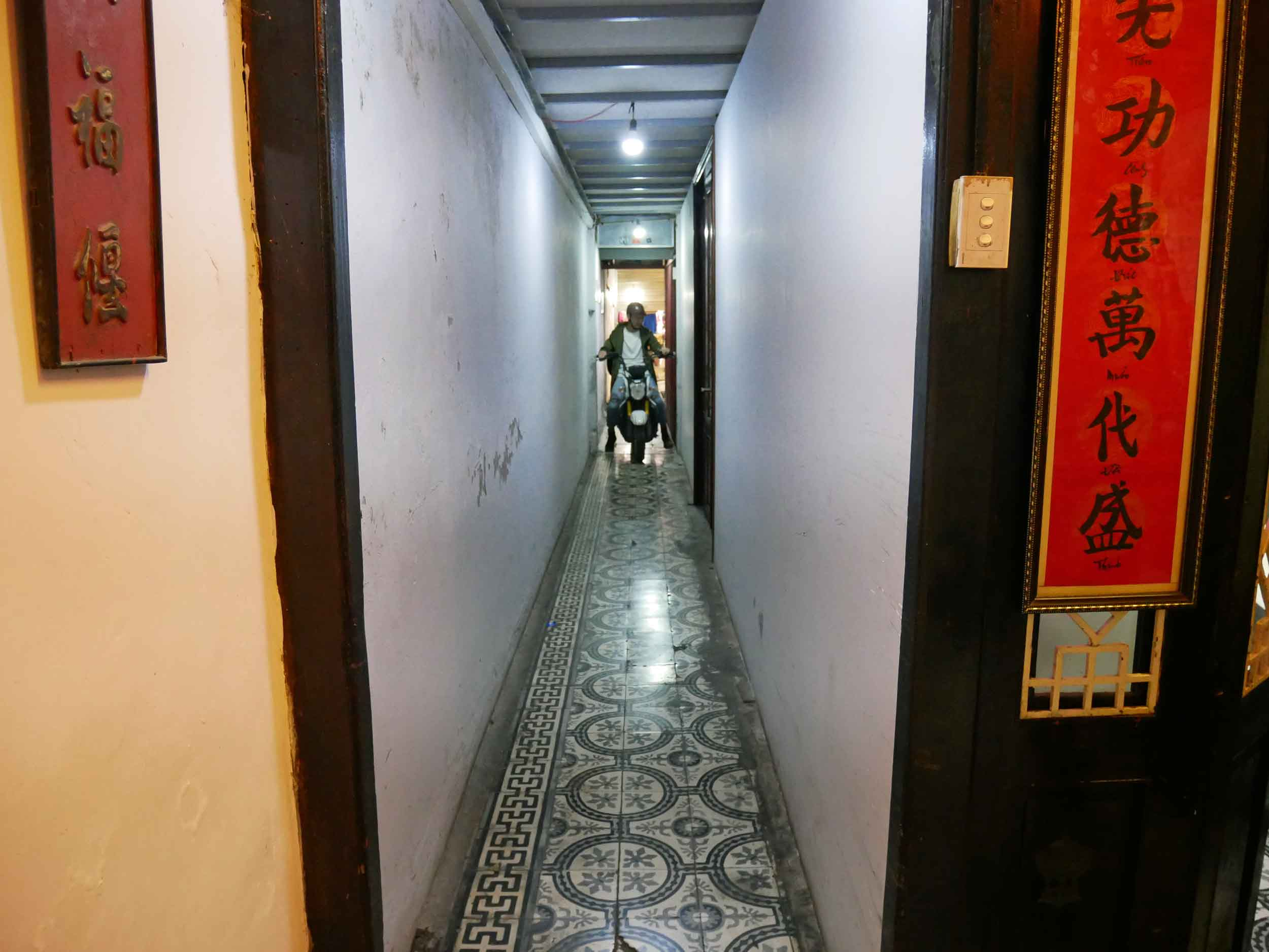 A biker tries to navigate the small alley to the cafe in back where he can park his motorbike.