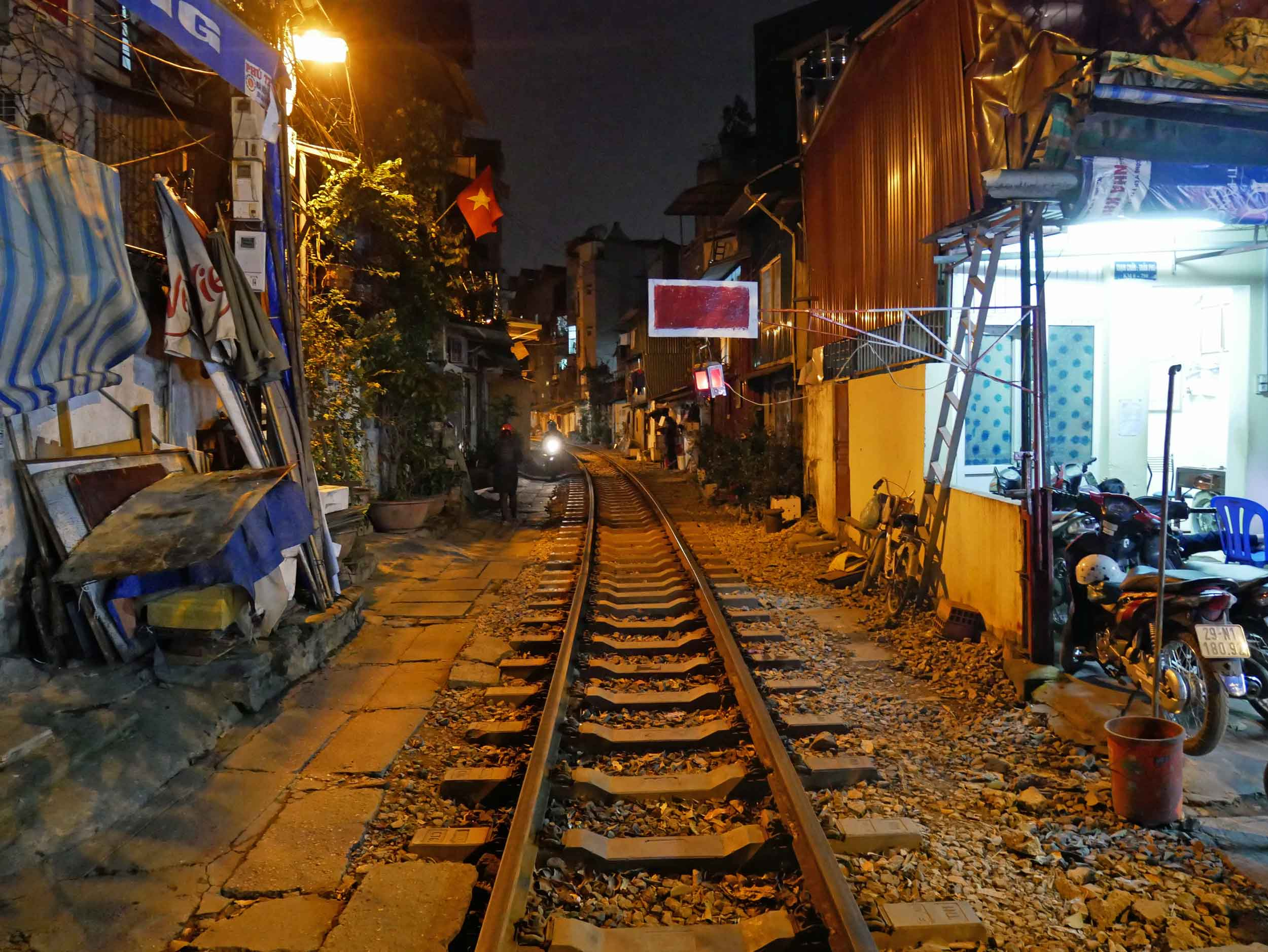 Nearby our hotel, trains still run through the crowded Old Quarter streets, causing locals to pull belongings inside according to schedule.