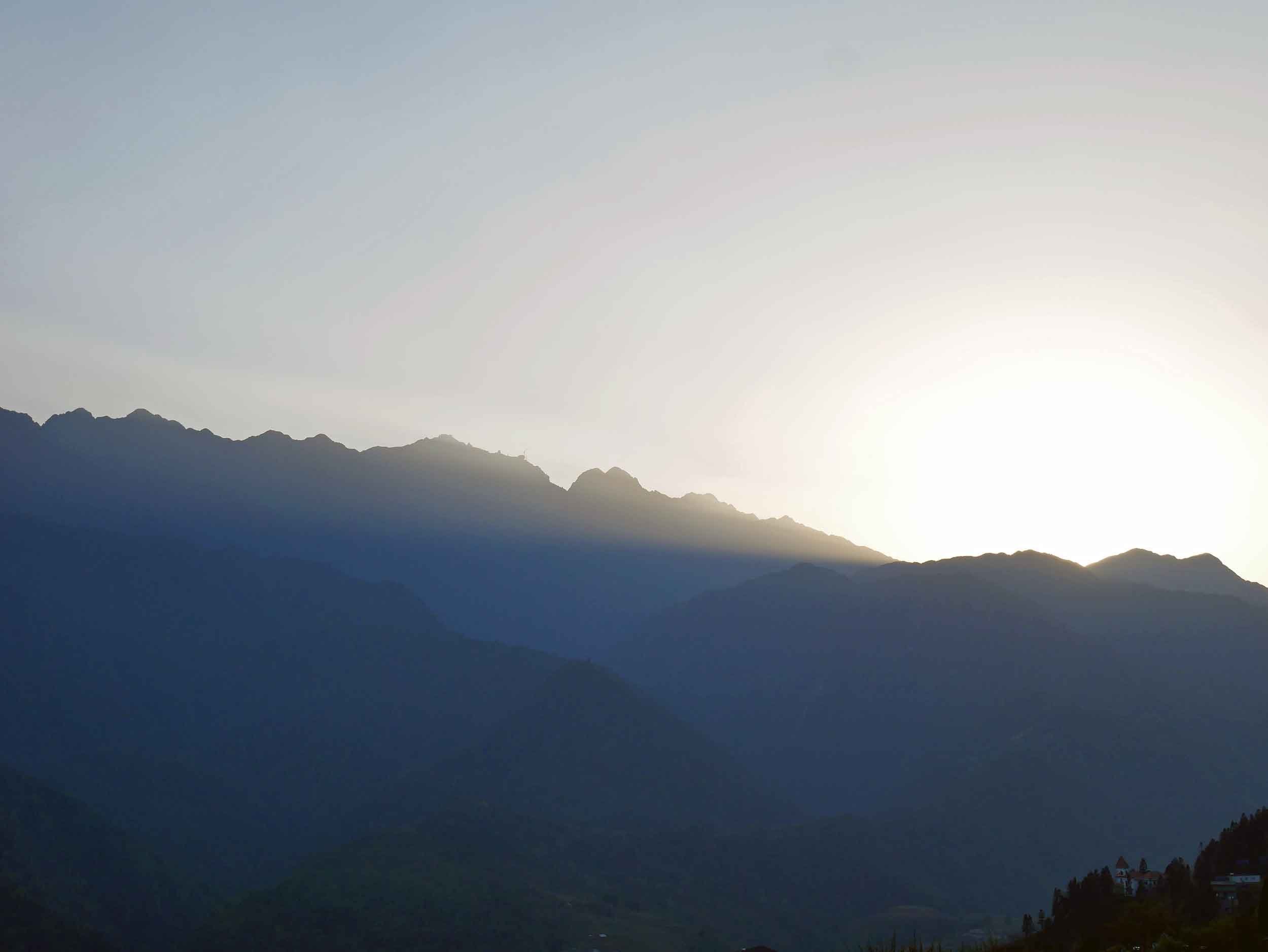 View from our hotel of the sun setting over the Hoàng Liên Son mountain ranges, which surround Sapa village (Mar 22).