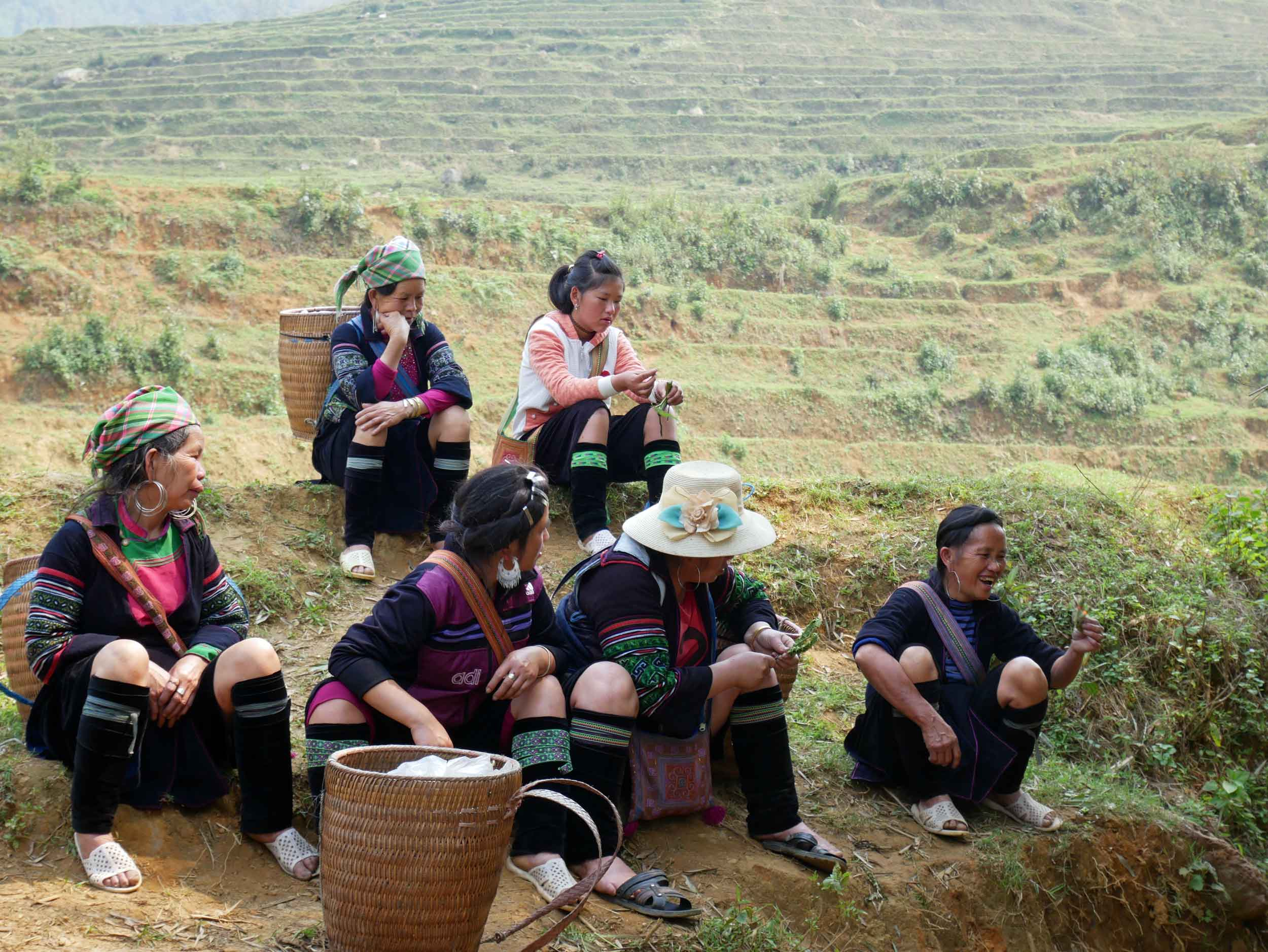 A group of gossiping Hmong tribeswomen briefly pausing from their daily commute with tourists (Mar 24).