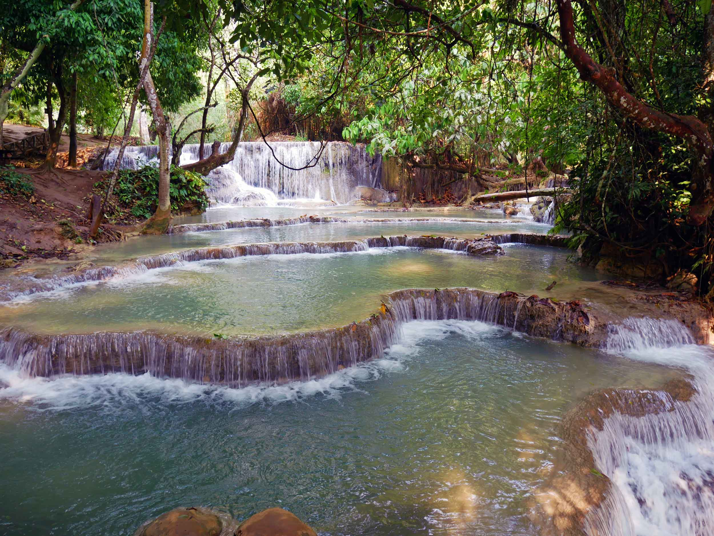 The many tiers and cascades are the result of travertine formed by the spring water of Kuang Si.