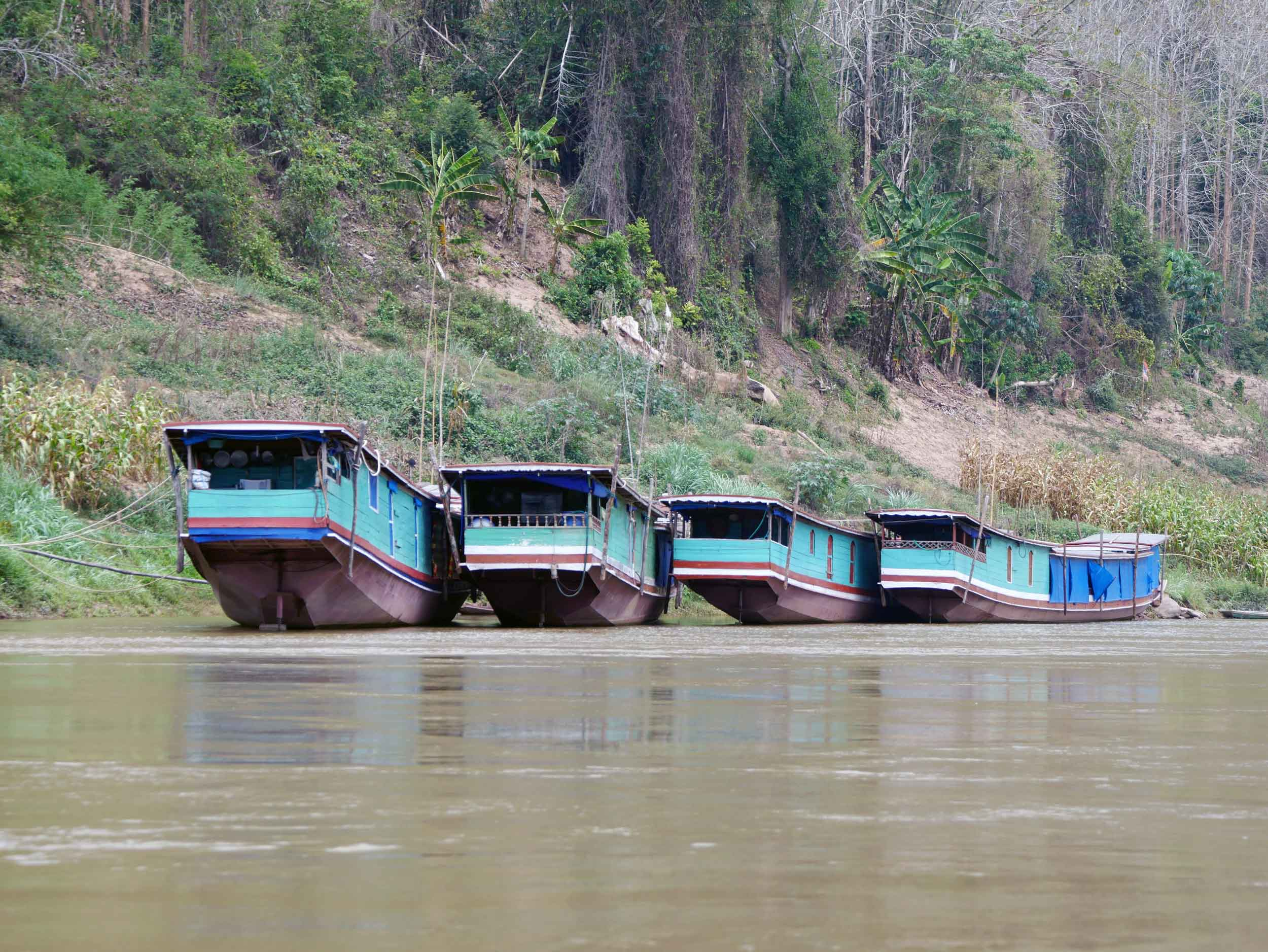 Several slow boats parked along the river's edge.