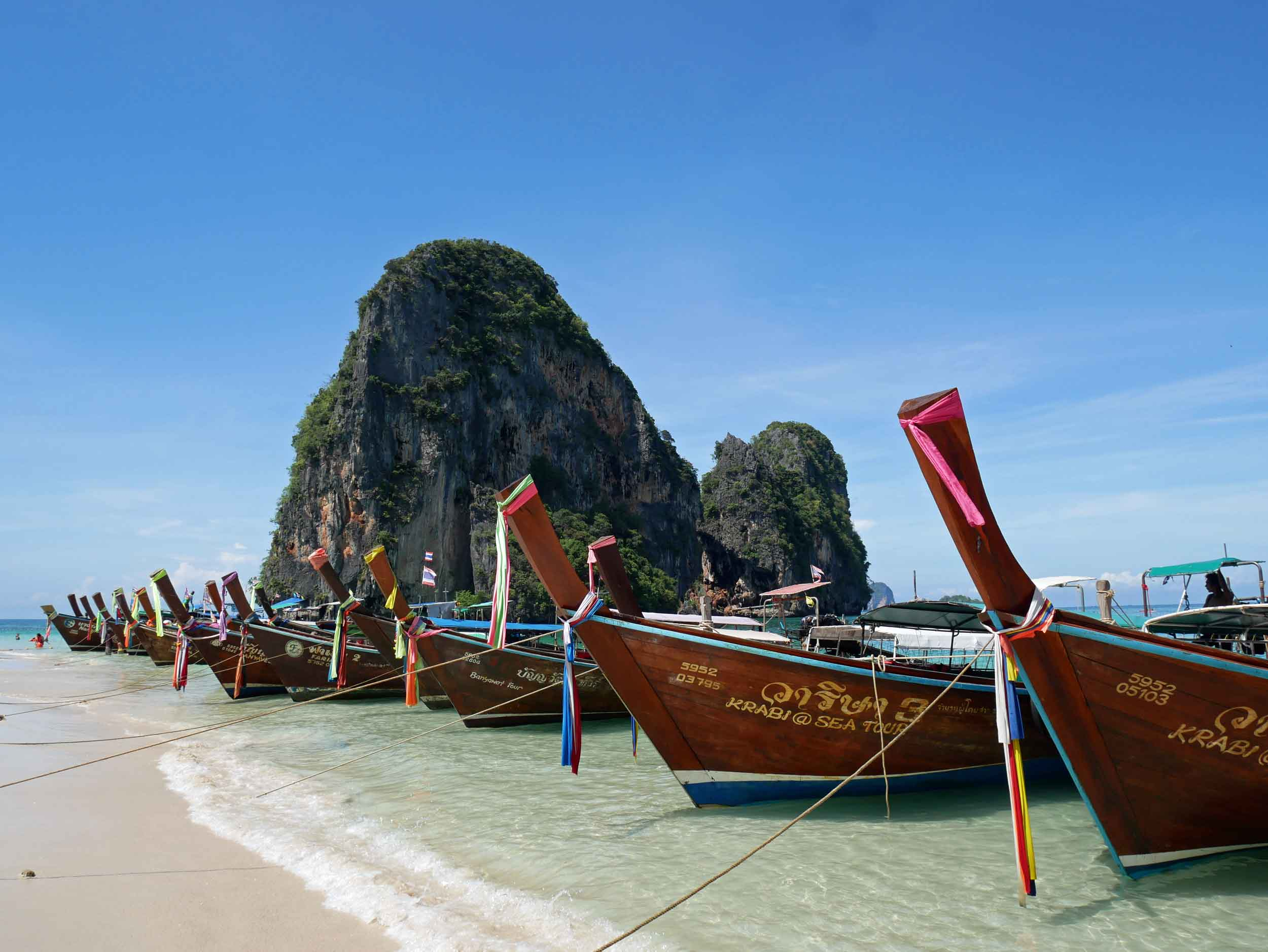 Long tail boats line the shore on a section Railay Beach, which is only accessible by water.