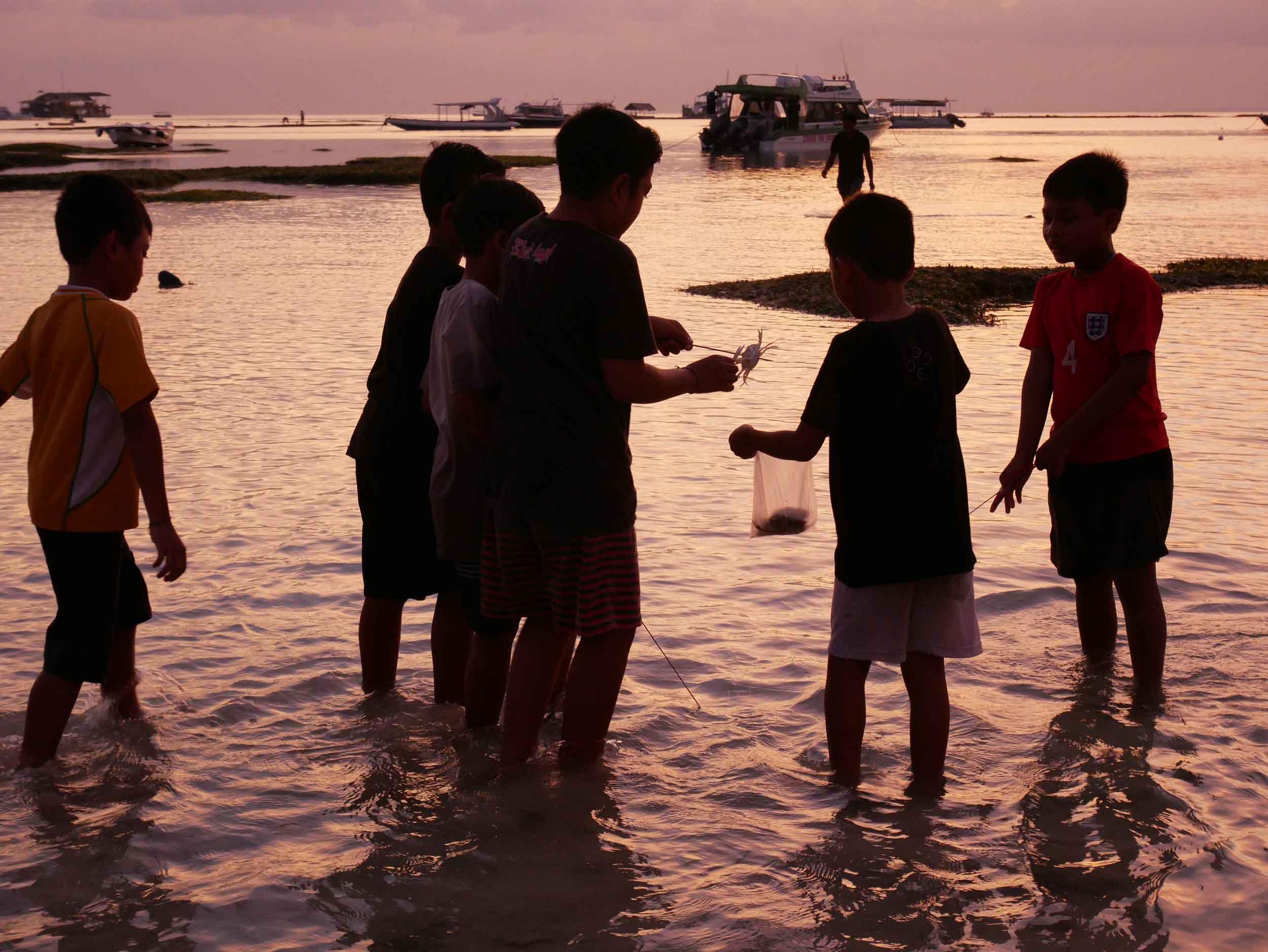 Young Balinese children playing and hunting for fish as we docked at sunset near Nusa Lembongan, Bali (May 14).