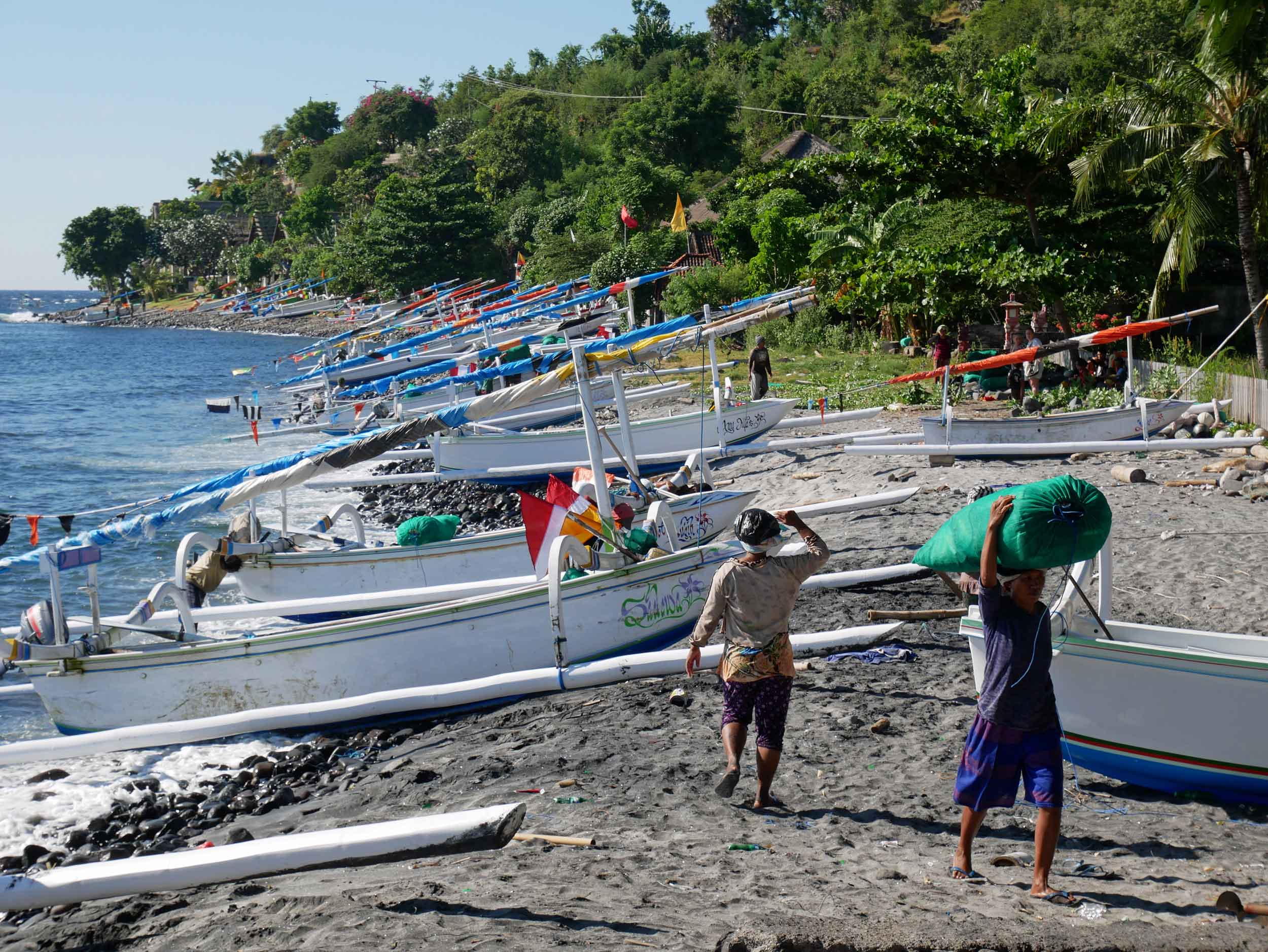 The fishing canoes lined up on shore as local women take in bags of freshly caught fish.