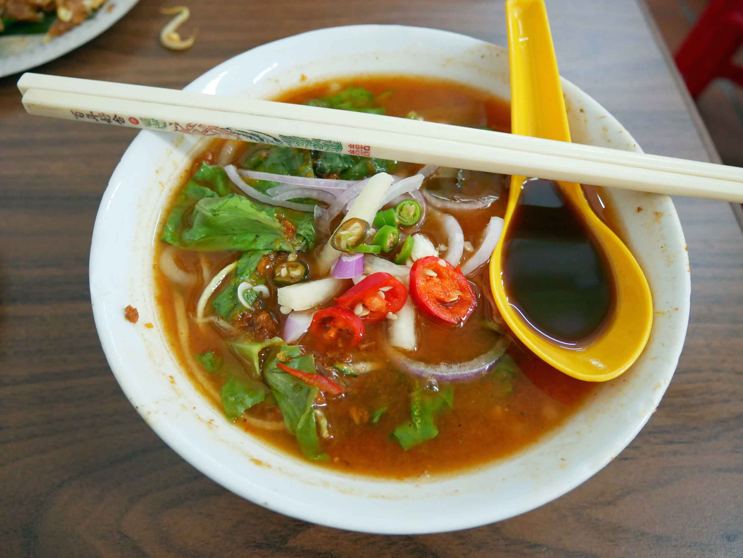 We slurped our way through a bowl of piping hot  laksa , a spicy noodle soup and another specialty.