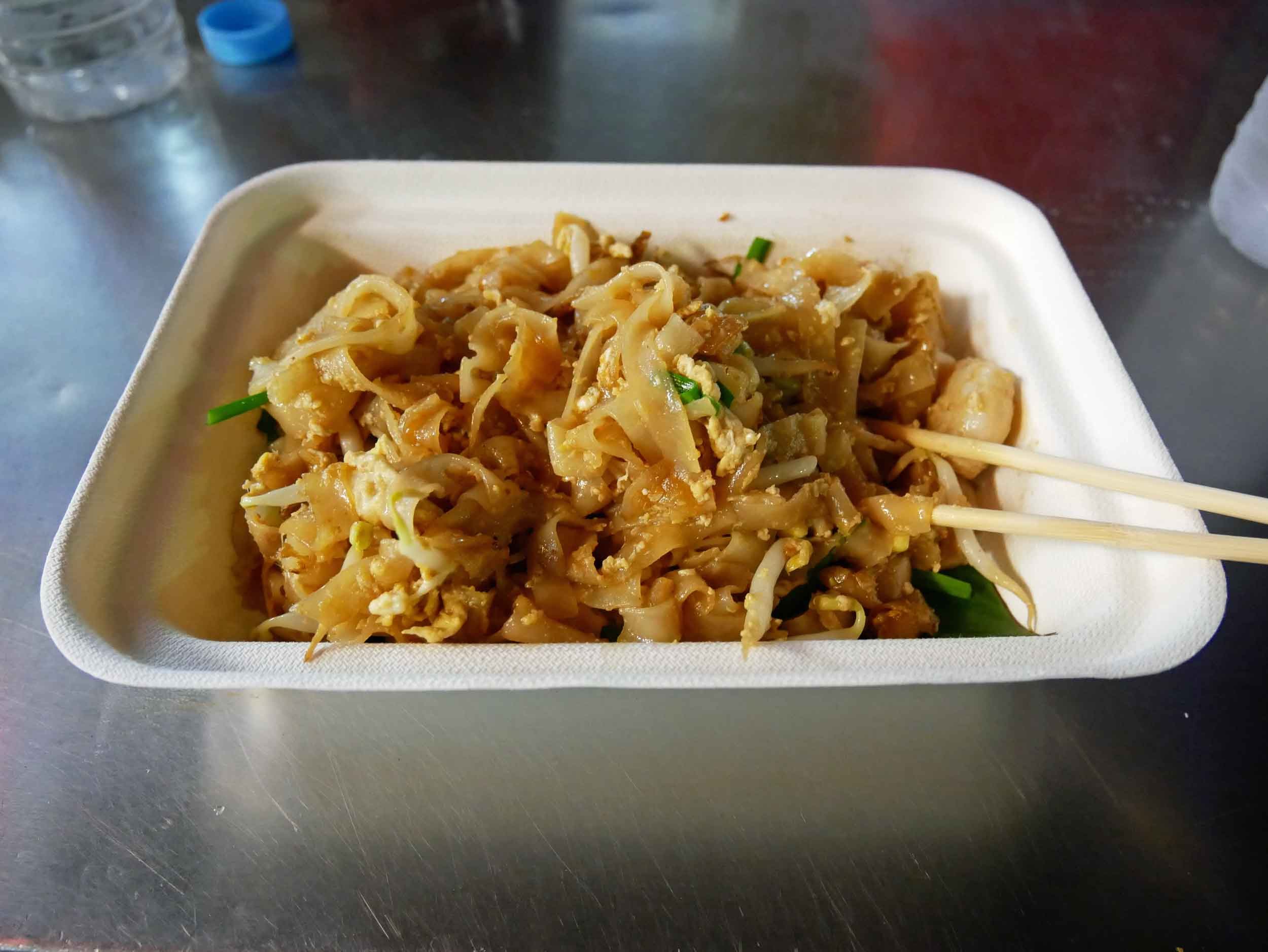A dish of Gurney's  char kway teow , a Pad Thai-like dish of rice noodles fried with shrimp, green onions, sprouts and egg in a wok.