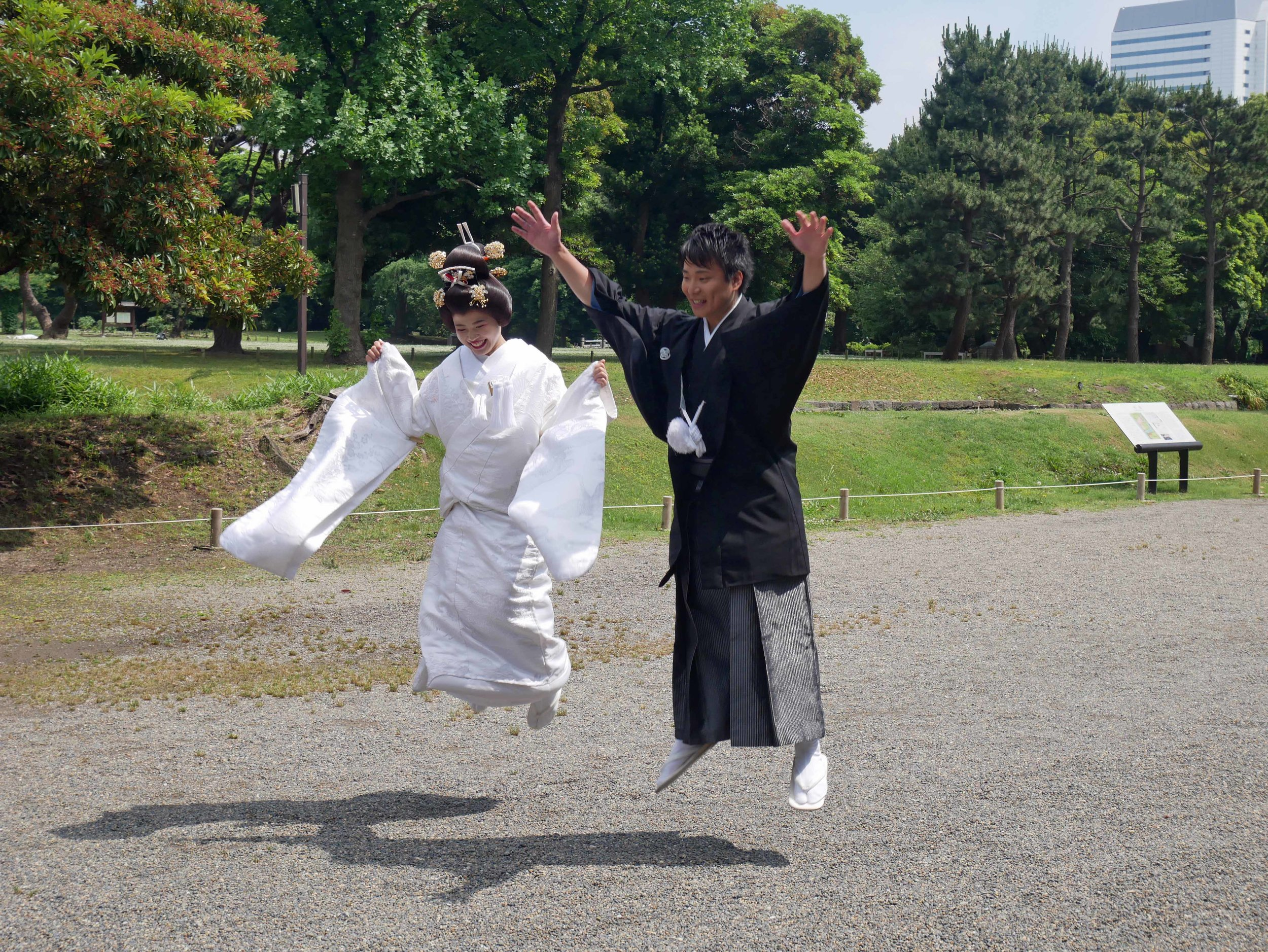 Just married! A couple in traditional national costume jump for joy in Hama-rikyu garden.