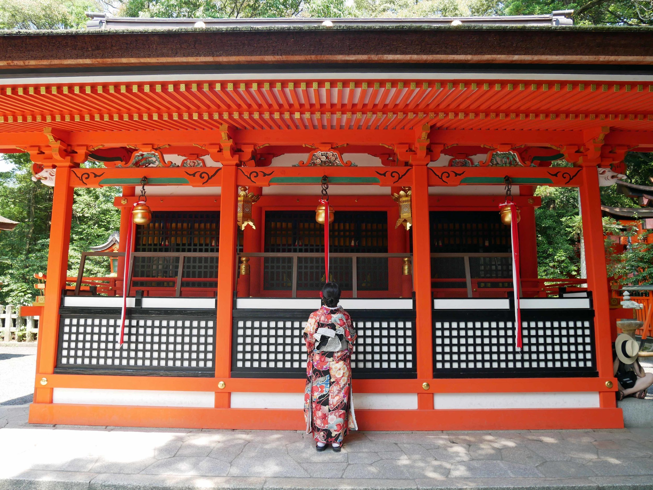 A Japanese woman makes an offering and prayer at one of the many shrines within the complex.