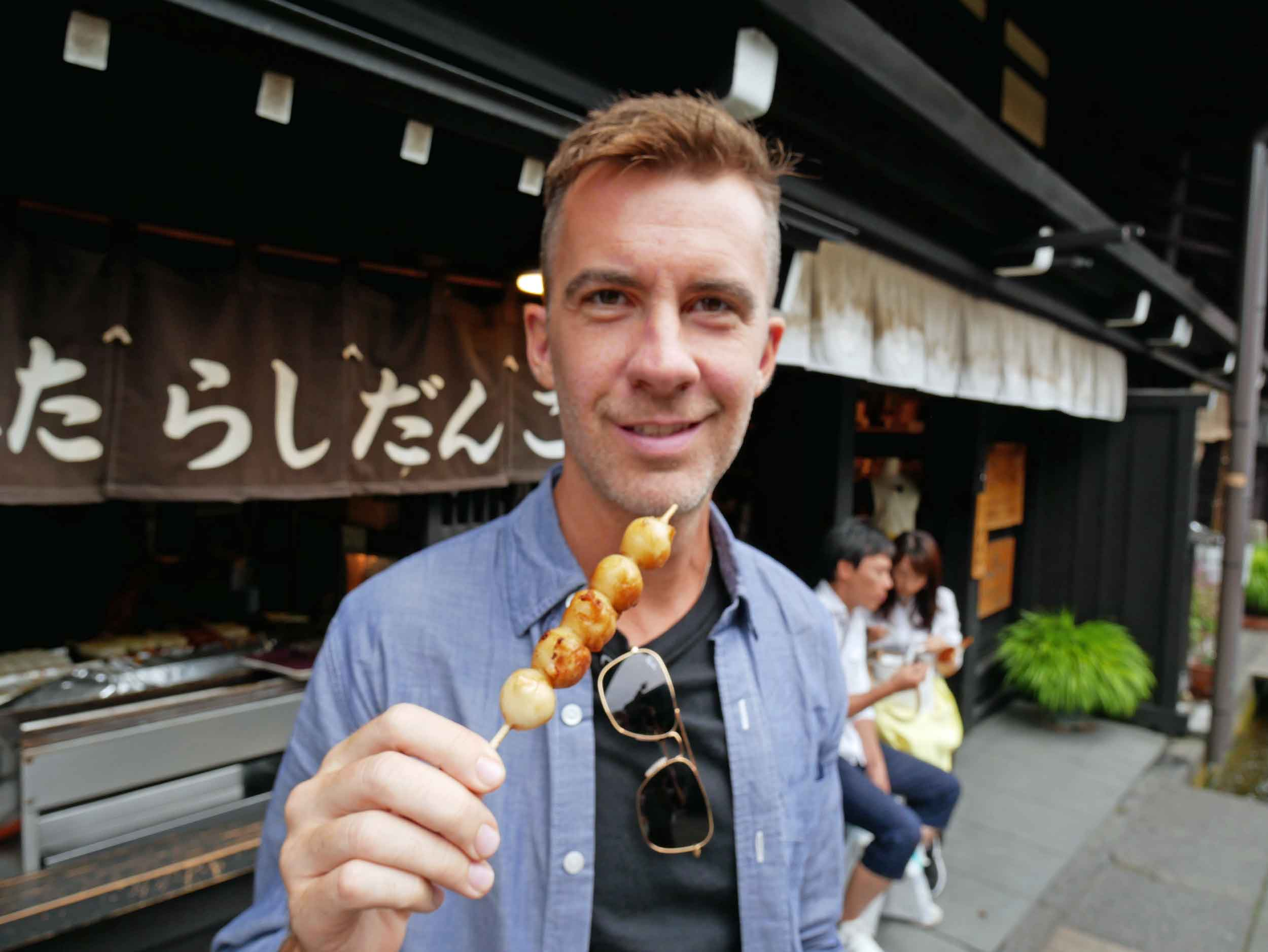 Trey attempts a skewered rice ball with soy sauce, one of the street food eats of Takayama.