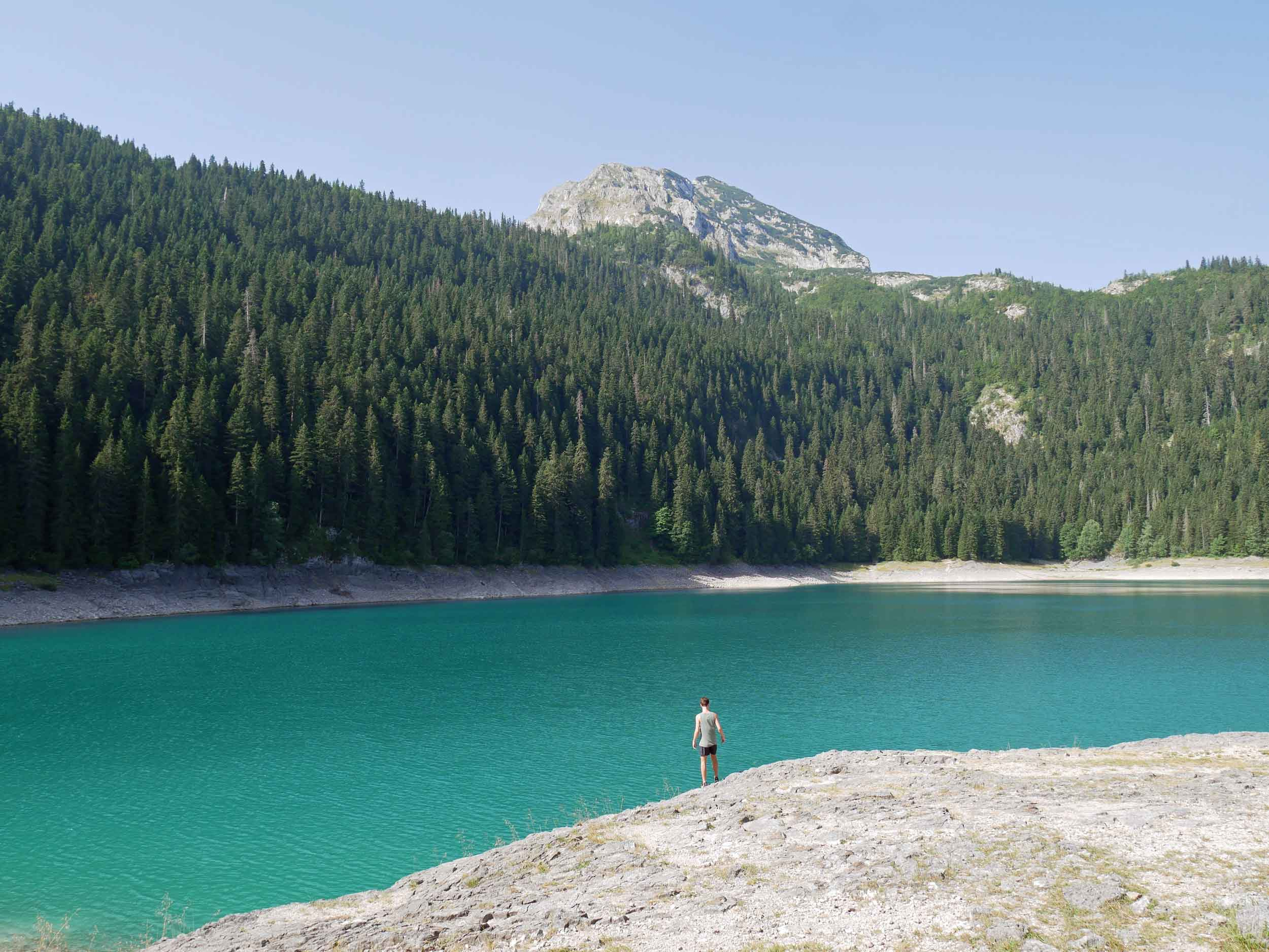 The calm waters of the Black Lake reflect the dark greens and blues of the evergreens and pines beyond.