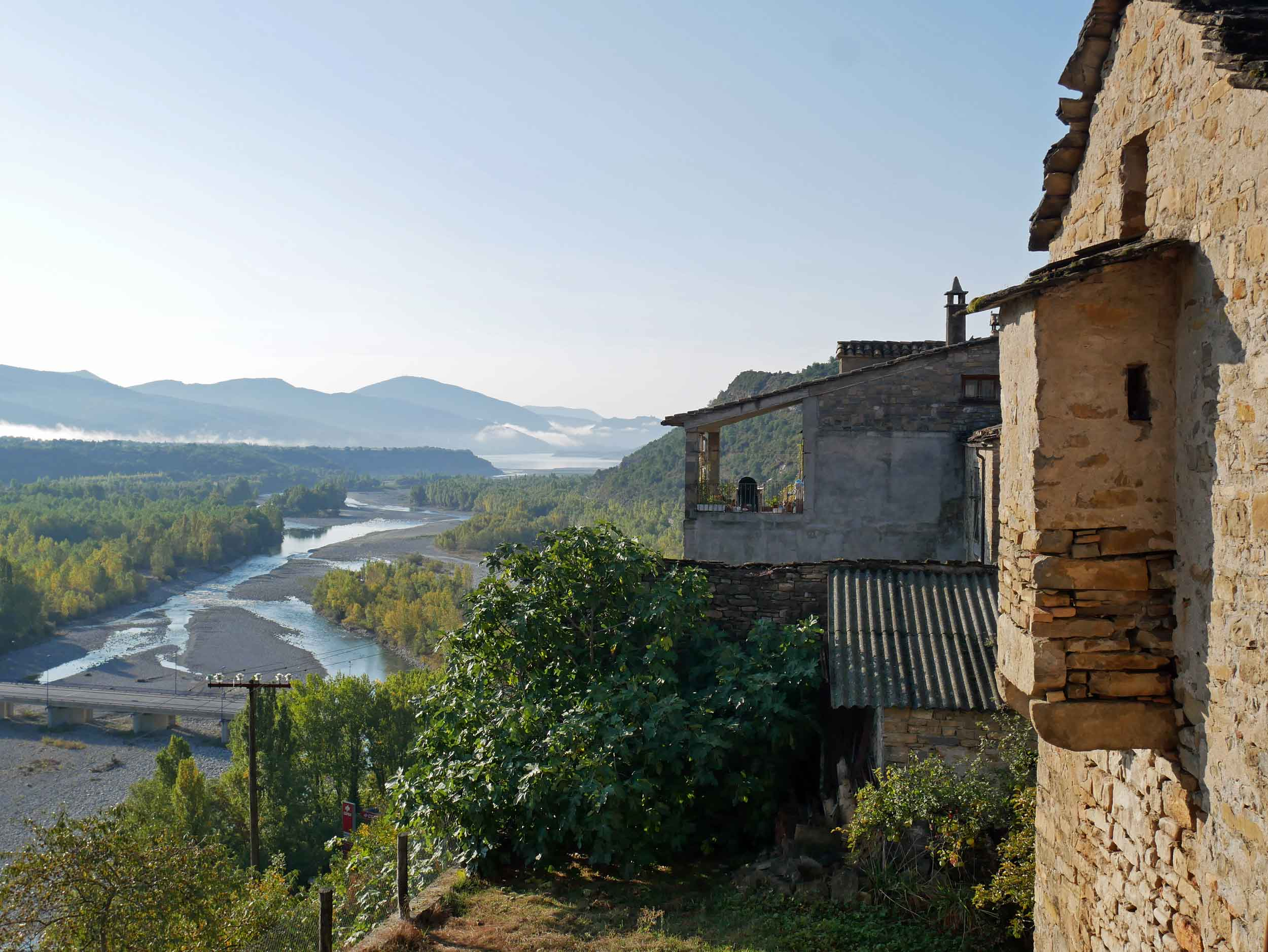 The village sits at the confluence of two rivers, the Cinca and the Ara, in the foothills of the Spanish Pyrenees in Huesca, Aragón.