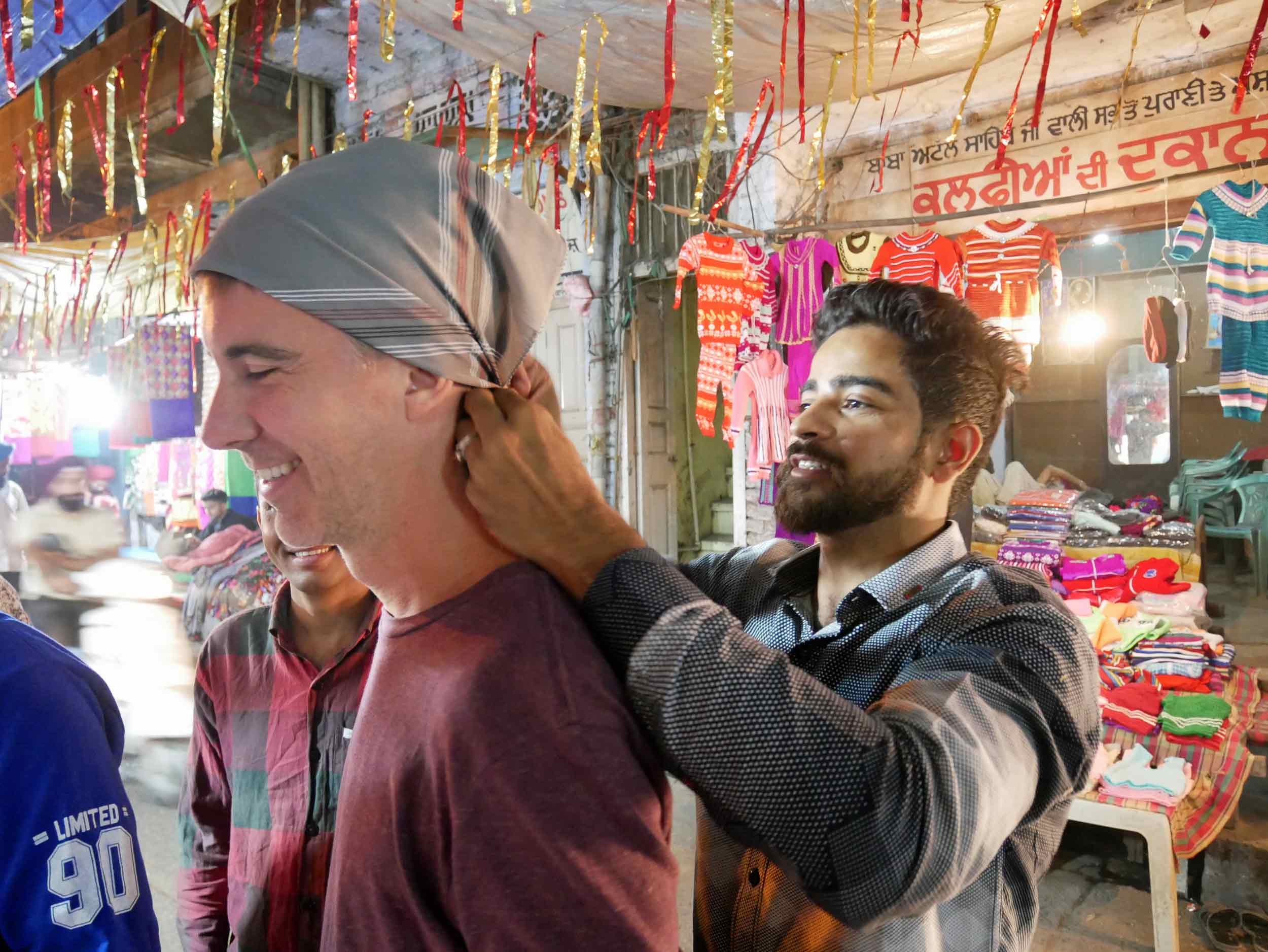 In order to enter the Golden Temple, men must cover their hair and remove their shoes – here, Trey gets fitted with a bandana.
