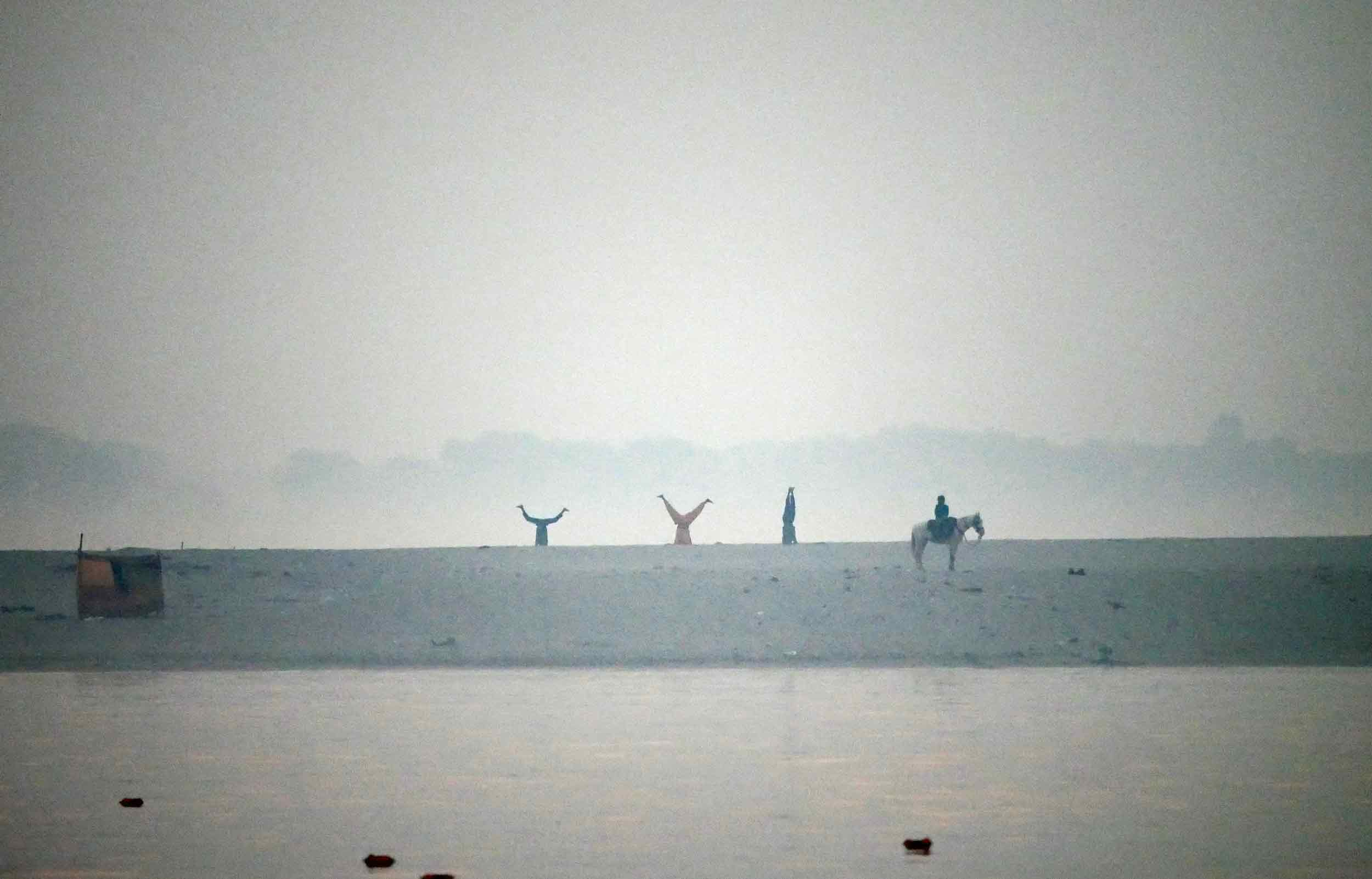 Yoga being practiced across the river on its sandy shore.