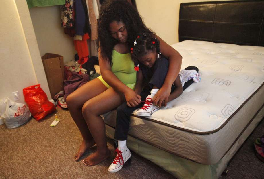 Carida Ward, 27, formerly in foster care, helps daughter Leilani, 5, lace her shoes to get her ready for school.