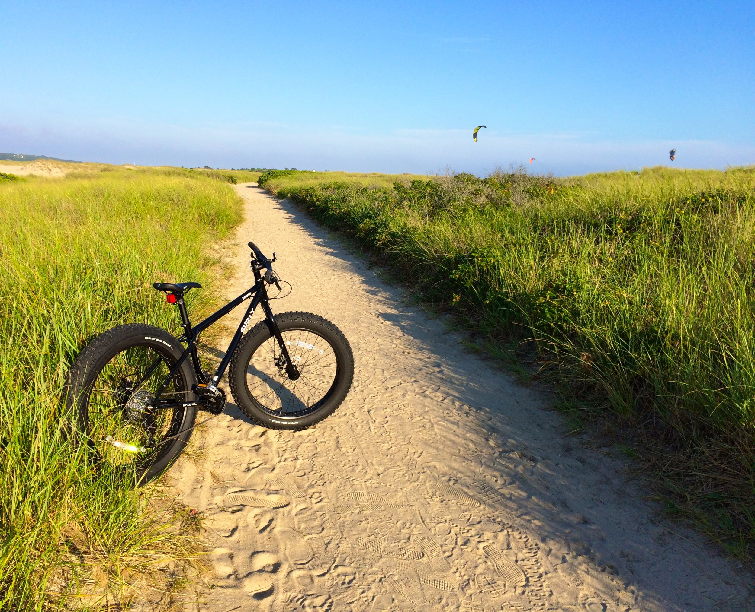 our Surly FatBike on the beach trail with Kiteboarders in the back ground