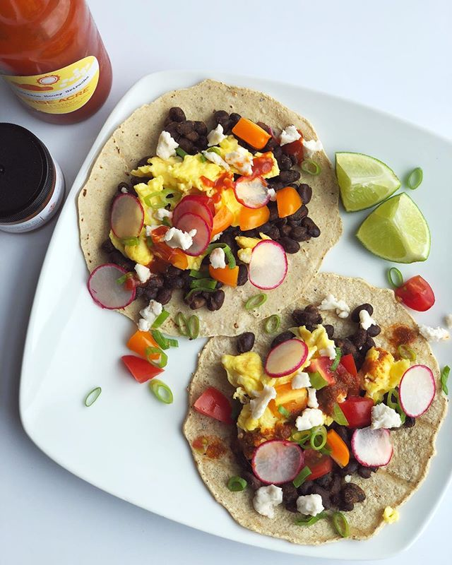Breakfast tacos! I am a creature of habit and on days I work I generally have the same thing for breakfast as it's quick, easy, and reliable. But I SO look forward to slow mornings off because I get to take my time in the kitchen and prepare something new! This morning I've got corn tortillas, black beans (simmered with cumin + paprika + cinnamon), scrambled eggs from @wiseacreeatery, cherry tomatoes, radish, green onion, @miyokos_kitchen vegan cheese, lime juice + 2 different sauces from LOCAL companies ♡ (Serrano Honey Sriracha from @wiseacreeatery and hot red Ethiopian chutney from @shahiya.chutney) Happy Friday, loves!