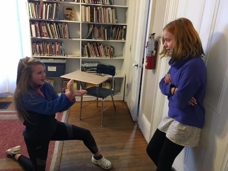 7th graders Lila Cobb and Cliona Balcom act out Zeus's proposal to Hera - and her negative reply - in Latin class, as part of their preparations for Mythology Day (December 21).