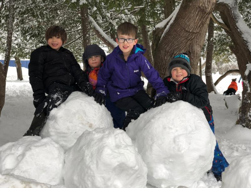 1st graders Raleigh, Julian, and Oden played with kindergartener Azro in the mounds of snow we have under the cedar trees!