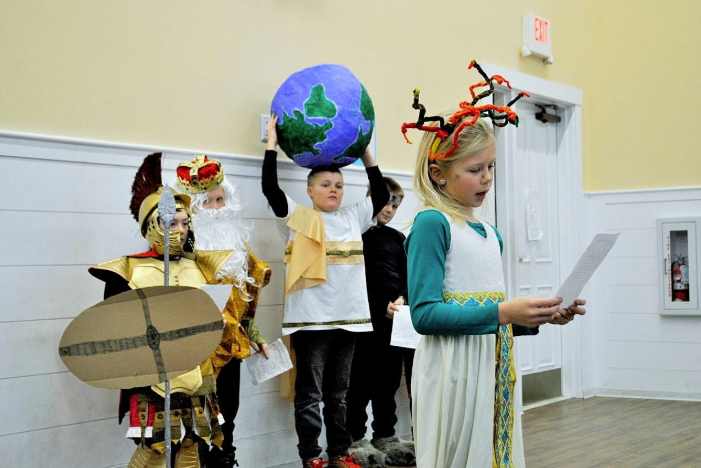 Riverside 3rd grader Rosa Patoine presented herself as Medusa in The Riverside School's morning assembly as part of the school's annual Mythology Day tradition.  In the background are other 3rd graders (l-r): Gabe Adams as Mars, Sawyer Daffinrud as King Midas, Clint Heinrich as Atlas, and Quinn Amidon as Polyphemus.