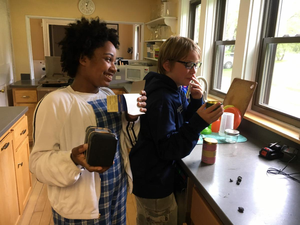 """6th graders Izzy and Sam work together to try and identify the hidden contents of a box, by comparing its odor to a variety of teas, as part of Mr. G's traditional """"Black Box Lab."""""""