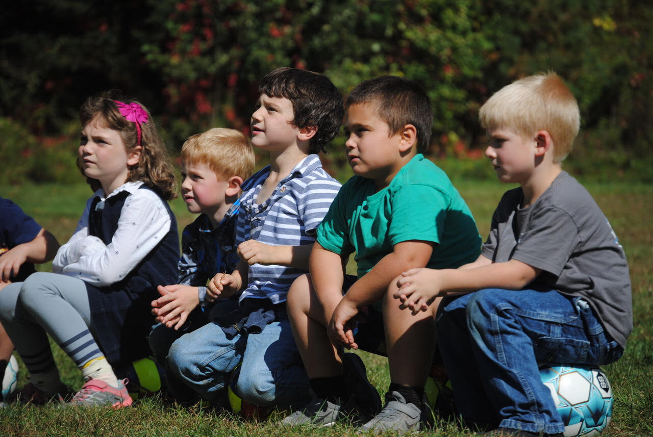Alice, Paul, Alex, Will, and Landen listened carefully to Sean's instructions for the next soccer skills game during K-1 PE recently.
