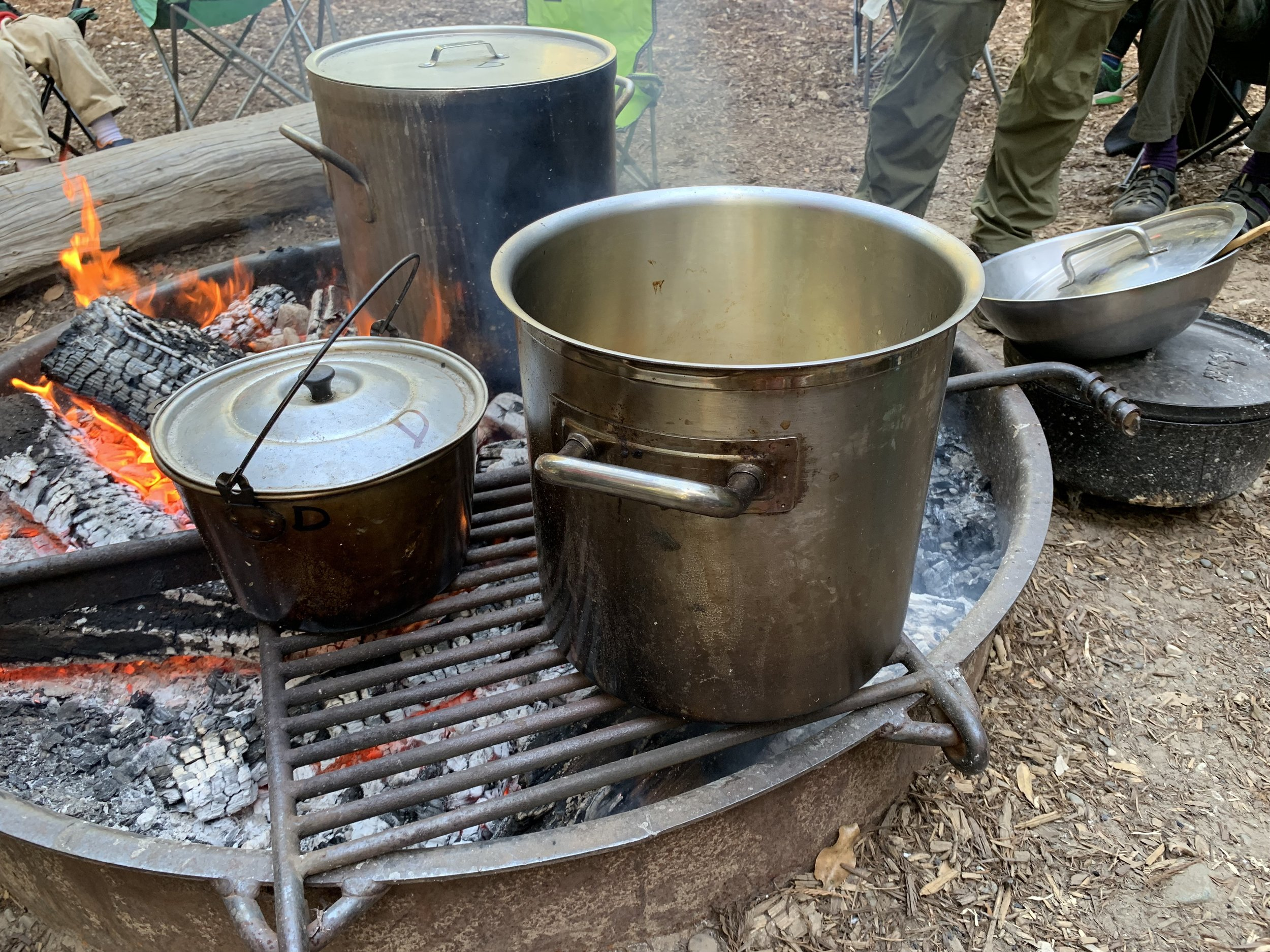 The crisp is in the dutch oven on the right waiting for it's turn on the fire.