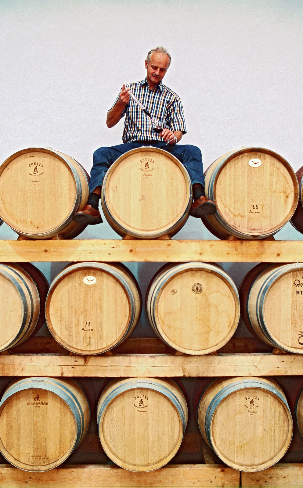y9740 - NOT TO USE FOR WINE ADVERTISING - GESPERRT FUER WEIN-WERBUNG - Spain, Valencia Region, Utiel-Requena, Bodegas Palmera, Organic viniculture, owner Heiner Sauer sitting on top of oak barrels testing his wine.