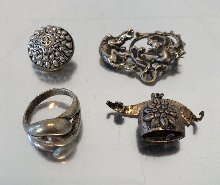 Clockwise from upper left: coat button, dragon pin, Innsbruck souvenir pin, silver ring