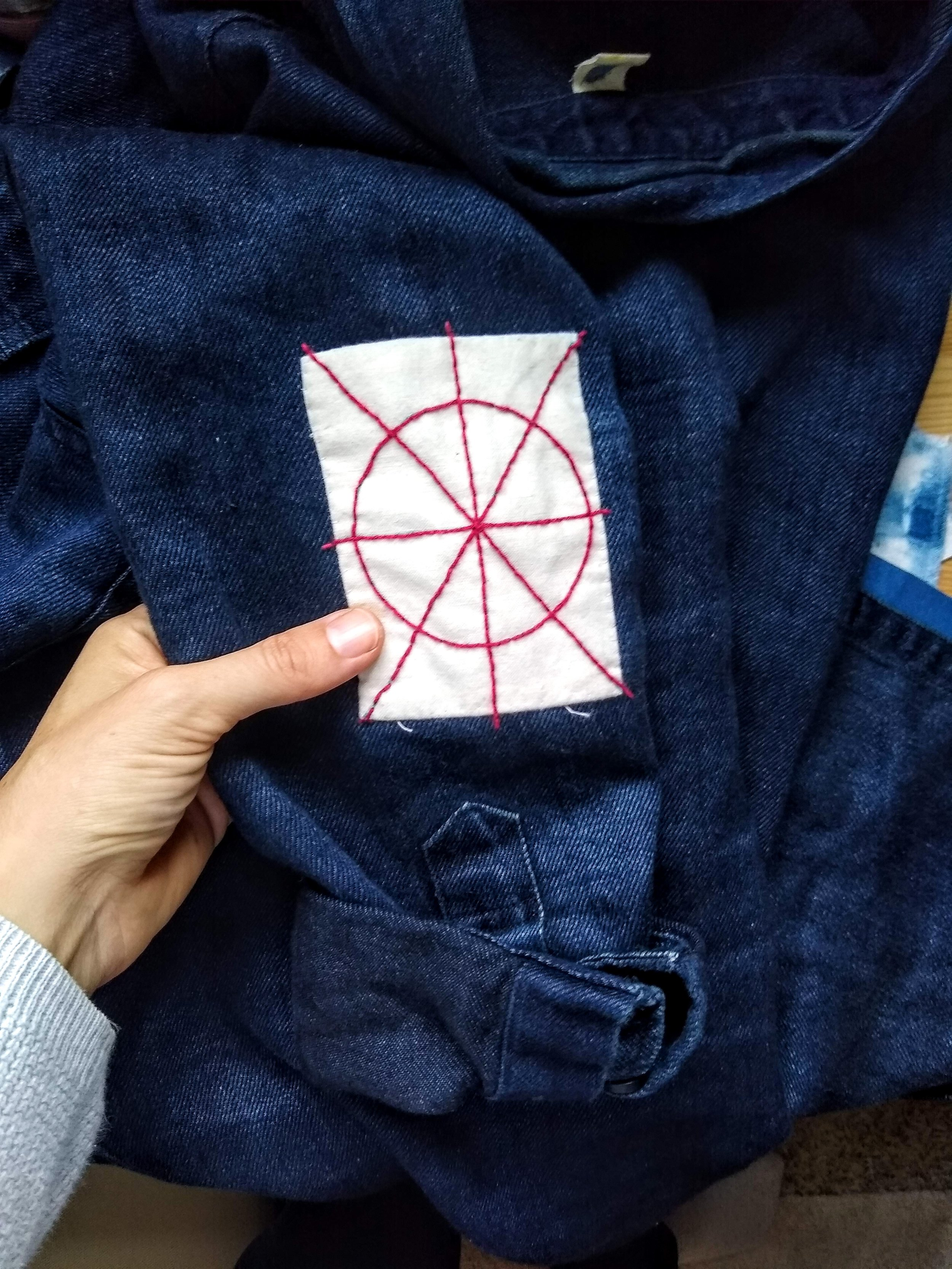 A basic fabric appliquéd patch with red sashiko top stitching to add strength and interest on an oversized denim shirt.
