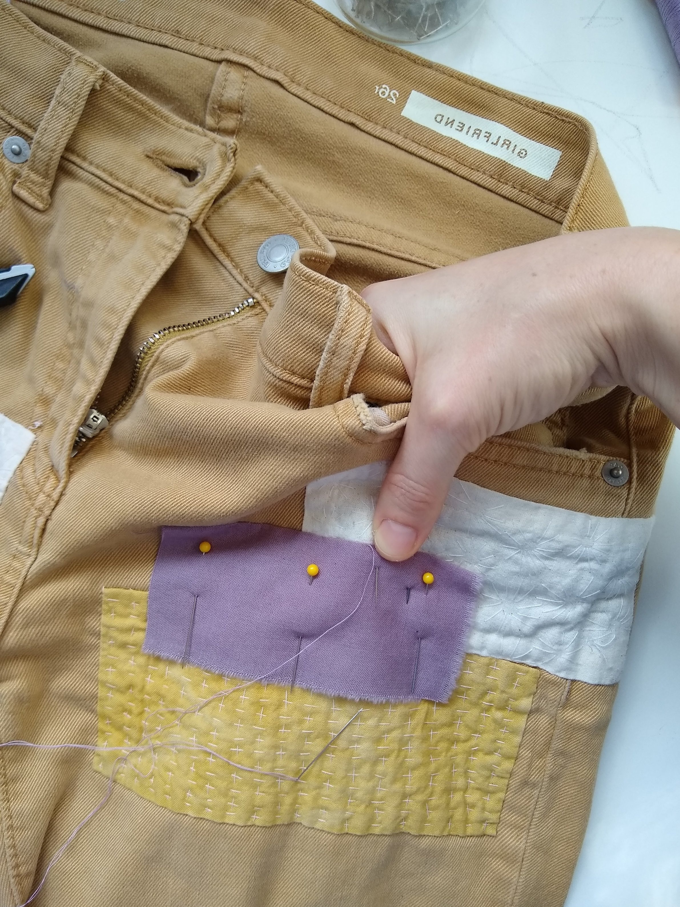 To get a good handle on your sewing, be creative. Slip a hand in a pocket or an arm up the leg of your mend. Just don't sew your pocket closed!