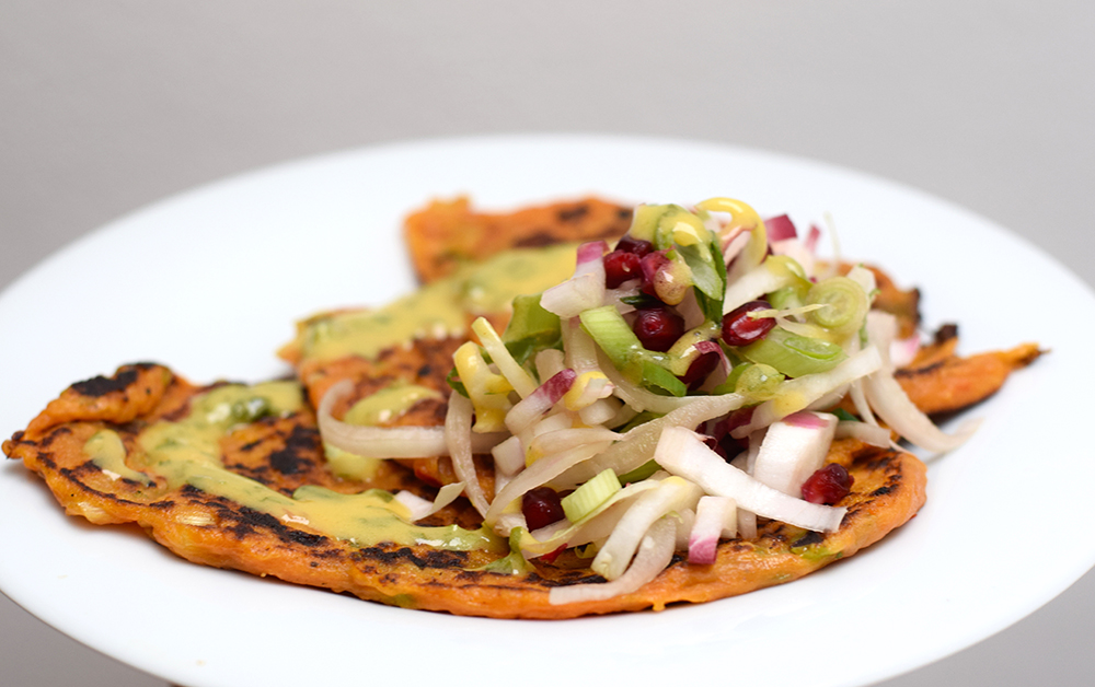Sweet potato, spring onion and chilli pancakes with a chicory pomegranate salad and grapefruit lovage vinaigrette