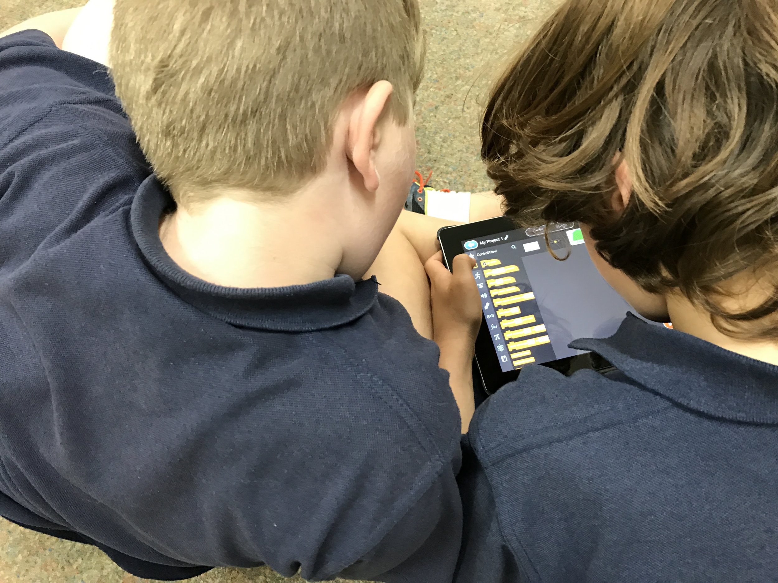 Two students using the iPad to code their drone.