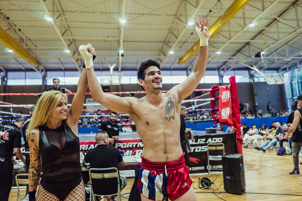 Seductively dressed ring-girl takes Carlos by the hand and brings him to the ring while the presenter El Niño Foca proudly announces the names of the fighters.