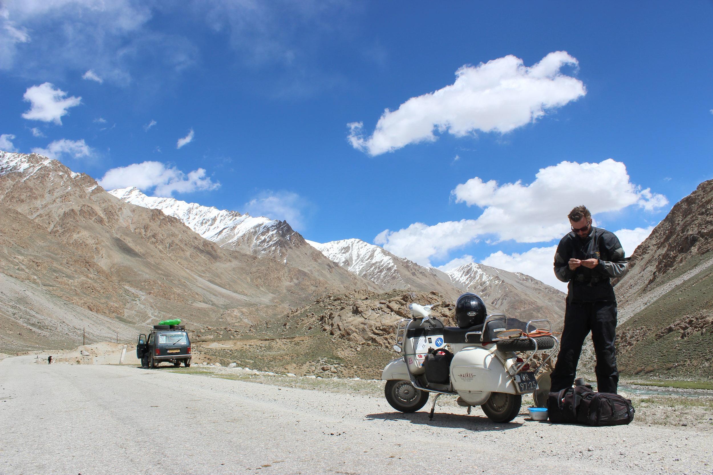 Laurens de Rijke doing maintenance on his Vespa GS160, picture taken on the Pamir Highway in Tajikistan.