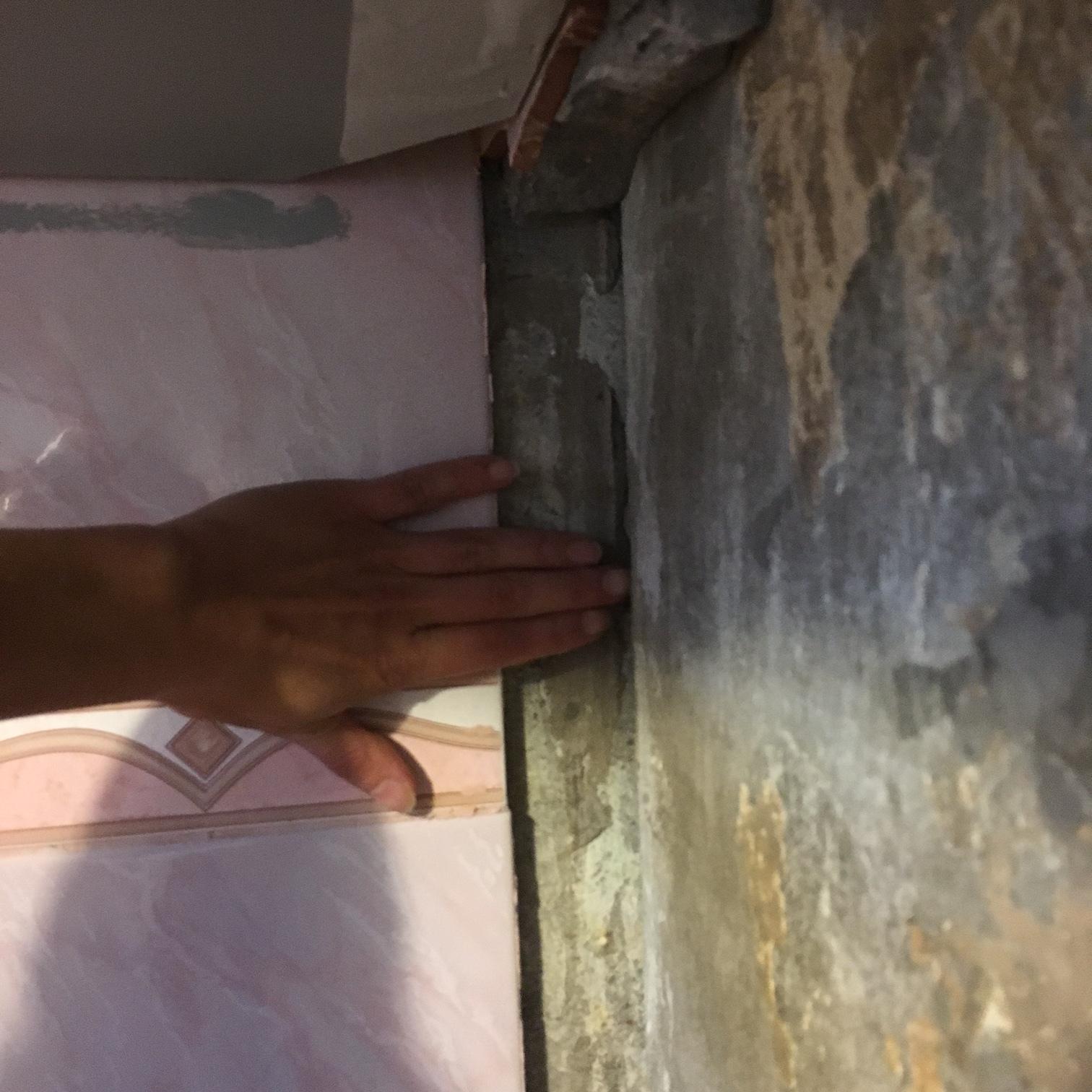 Вот такой был перекос стен. Сверху видно кусок кафеля и толстый слой клея под ним