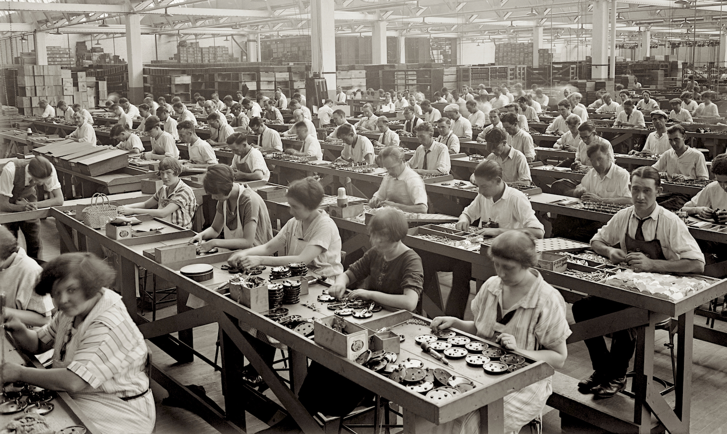 Workplace seating in the Industrial Age. Shop floor at the Atwater Kent Radio Factory, Philadelphia. 1925. Everett Historical Collection.
