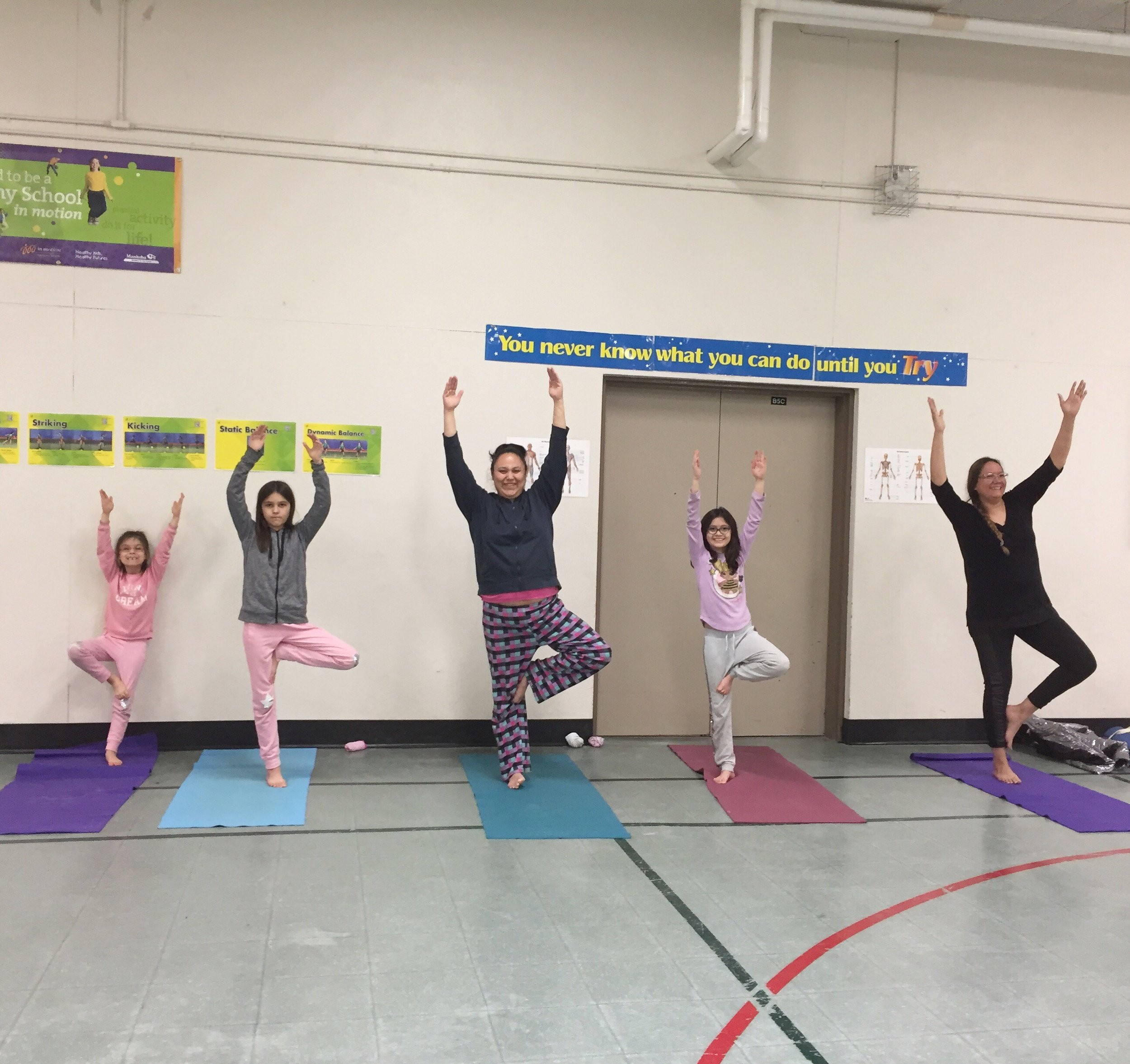Trees in bloom at Dufferin School in the after school family program .  Yoga Centre Winnipeg instructor Marilyn Koss caught these beautiful tree  poses on camera .