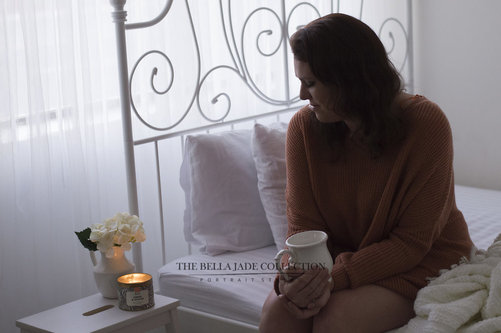 Natural Light Bedroom Boudoir Picture of Woman with Candles in Over-sized Sweater taken in Phoenix AZ by The Bella Jade Collection Boudoir Studio