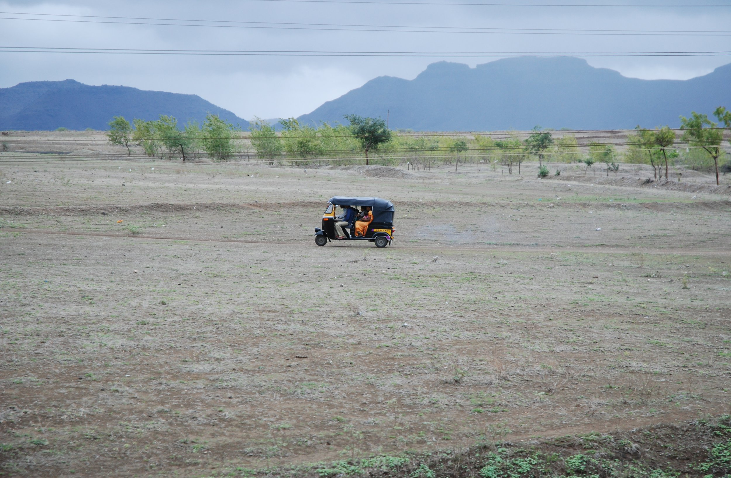 Autorickshaw in landscape.JPG