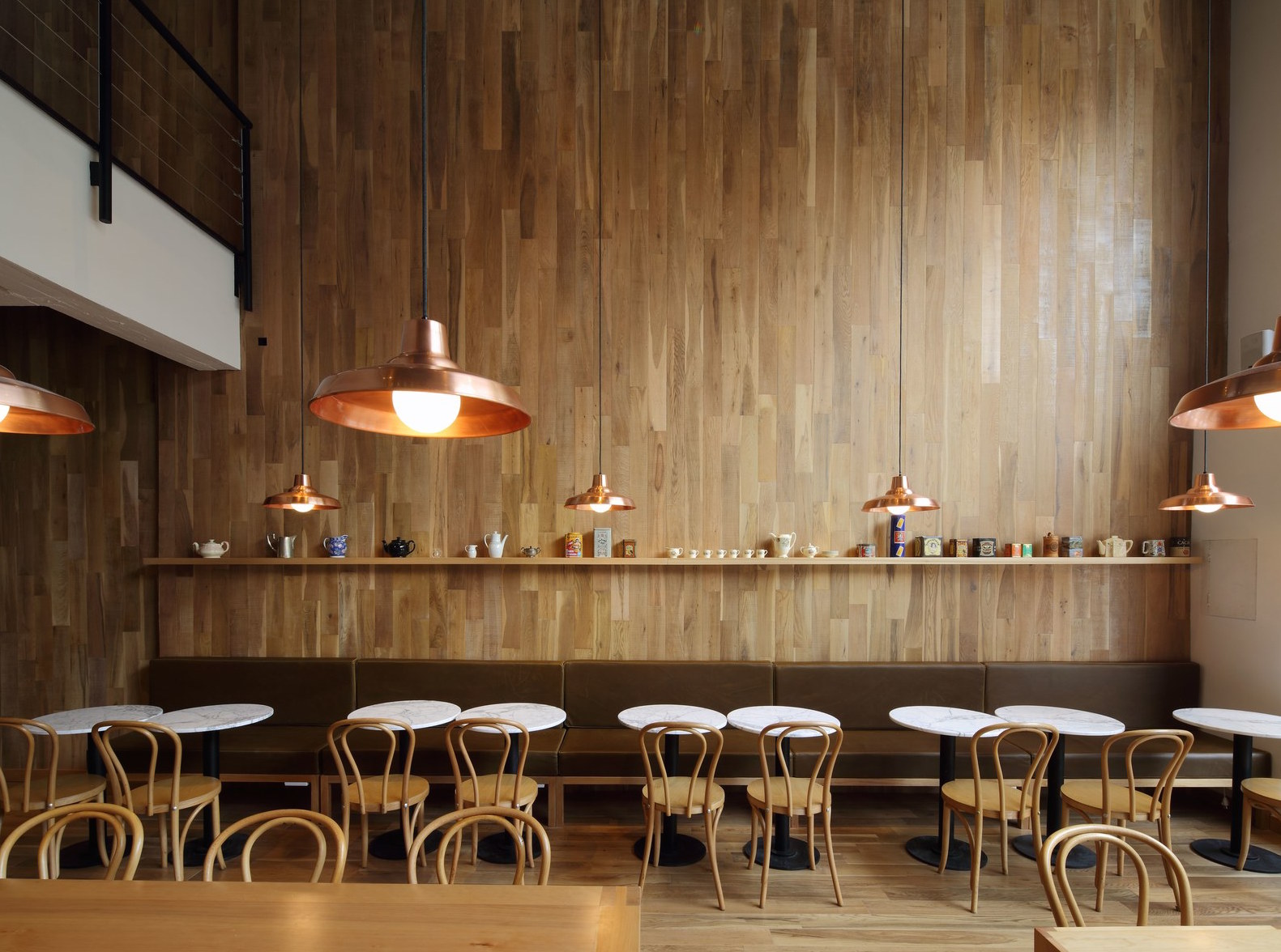 Blond wood, copper pendants, and a long chocolate banquette at merienda mainstay Ninina Bakery