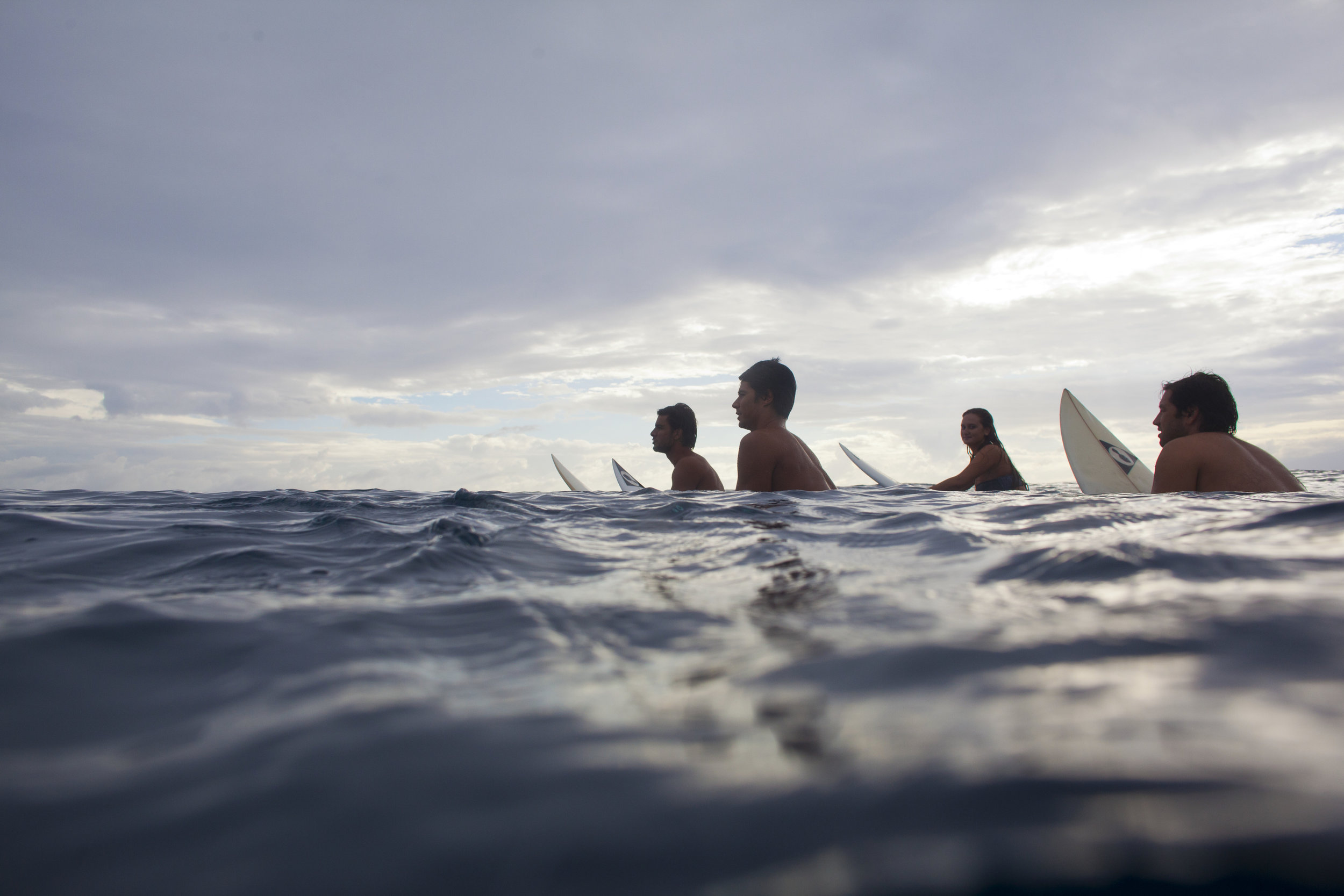 Surfers waiting for the perfect wave in Tahiti