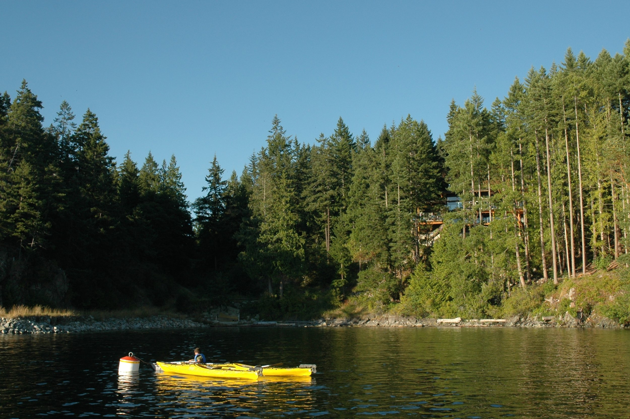 Mooring buoy with house in the trees above