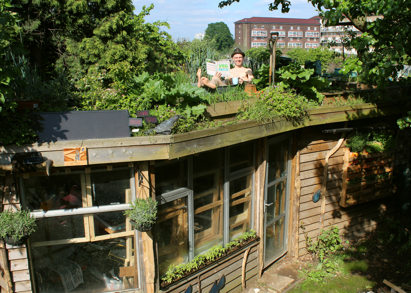 Joel Bird - Featured Artist for The Architect's Shed, sitting atop his own winning 'Allotment Roof Shed' in a tin bath drinking tea!