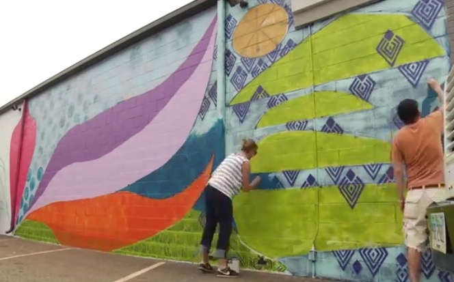 Sarah Dugger and Jon Stucky working on the mural at Be Yoga.jpg