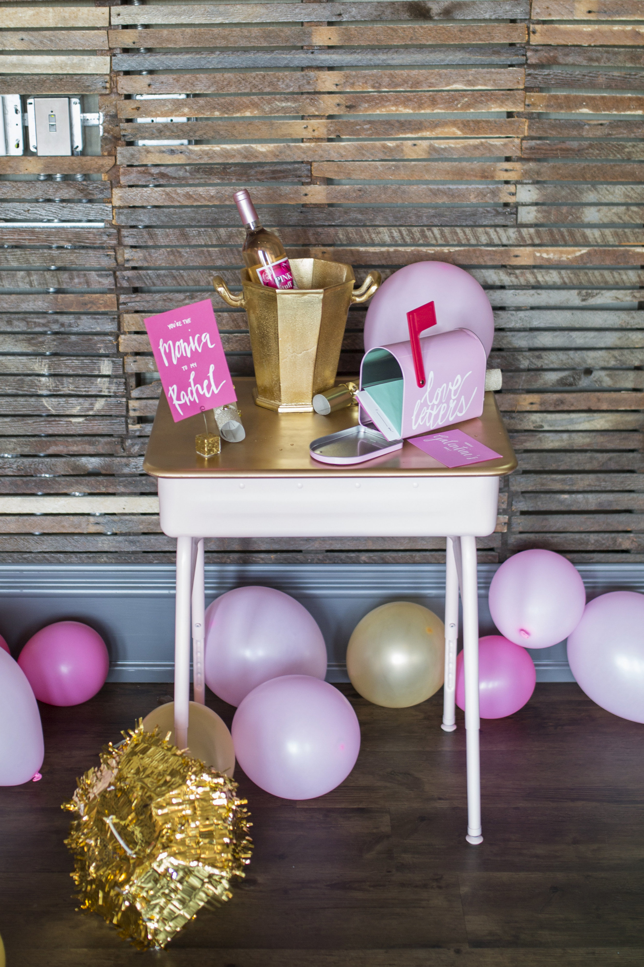 "This desk? A $5 thrift store find that I spray painted pink and gold and used as a ""love letters"" station. One of my favorite touches to add was the ""You're the Monica to my Rachel"" calligraphy sign courtesy of Scripted Reverie."