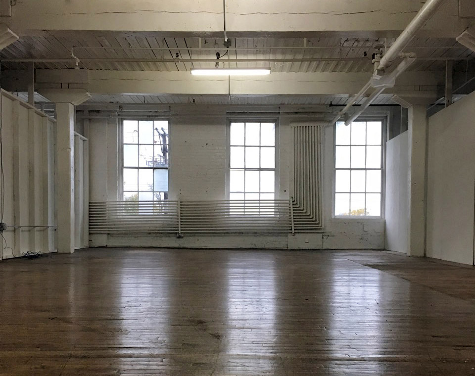 One of our empty studio spaces with north light windows, hardwood floors, high ceilings and a funky artistic vibe!